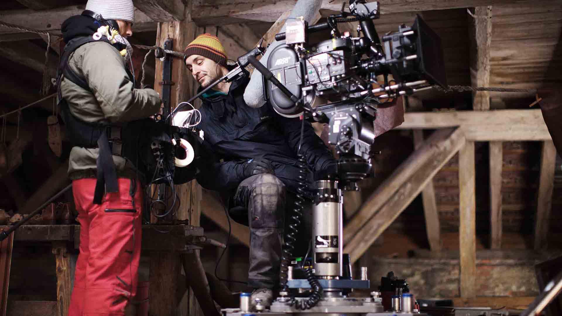 Das Bild zeigt einen Kameramann. Er steht vor einer großen Kamera. Neben ihm steht eine Frau und die beiden befinden sich in einem Raum aus Holz. Das Bild dient als Sliderbild für den Portfolioeintrag Eine gute Geschichte von Panda Pictures.