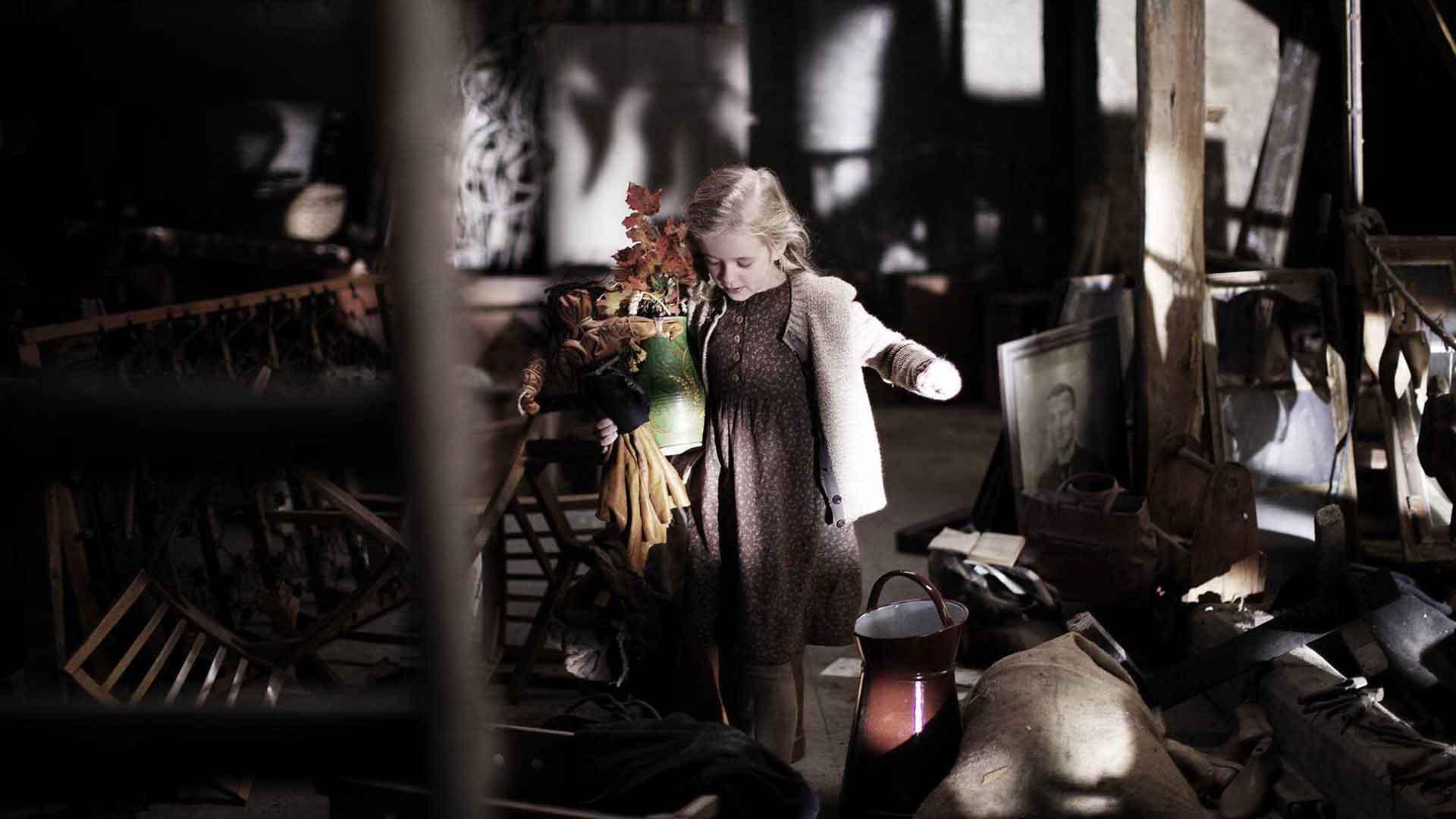Das Bild zeigt ein kleines Mädchen. Es hat blonde Haare und trägt einen Strauß Blumen in einem Krug. Sie läuft durch einen Raum voller Antiquitäten. Das Bild dient als Sliderbild für den Portfolioeintrag Eine gute Geschichte von Panda Pictures.
