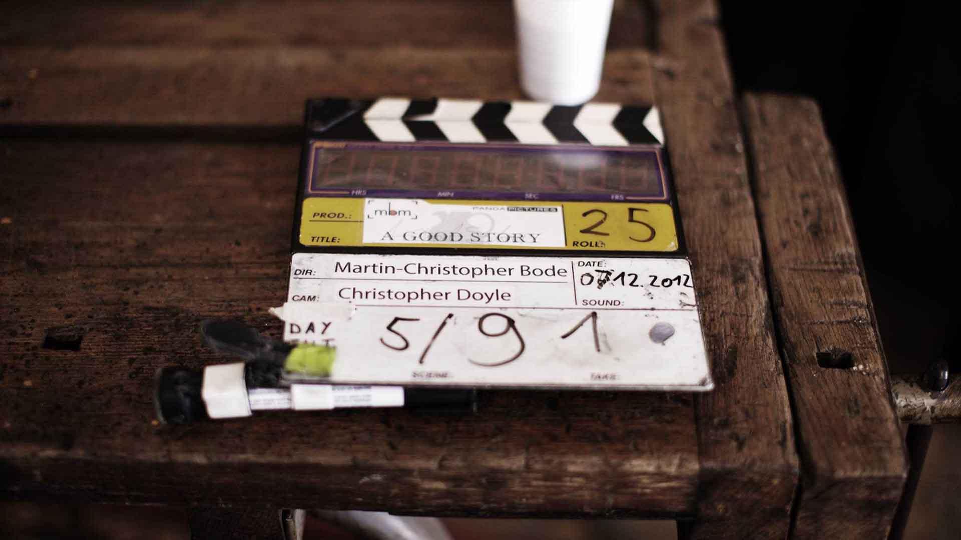 Das Bild zeigt eine Filmklappe die auf einem Holztisch liegt. Auf ihr sieht man die Zahlen 5/91. Das Bild dient als Sliderbild für den Portfolioeintrag Eine gute Geschichte von Panda Pictures.