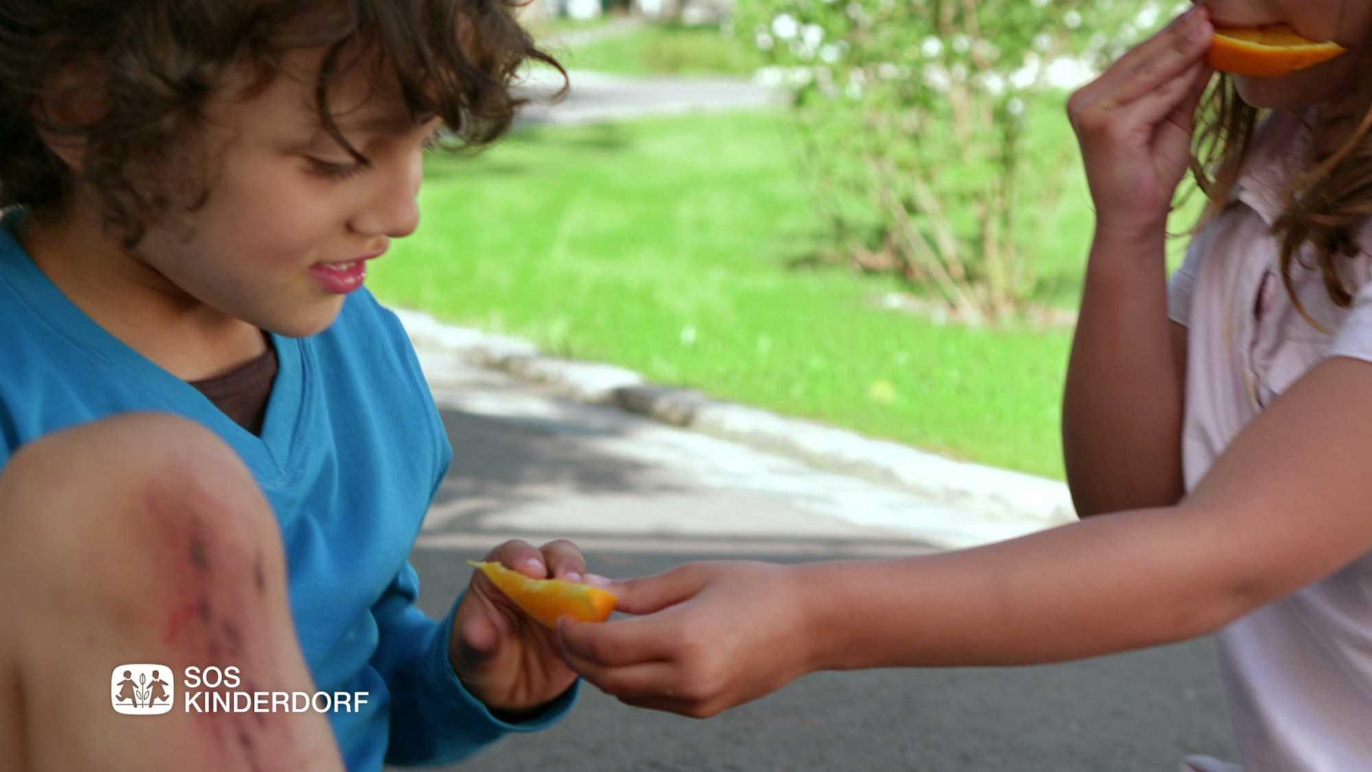 Das Bild zeigt zwei Kinder. Auf der rechten Seite steht ein Mädchen, es streckt eine Orange zu einem Jungen der auf der linken Seite steht hin. Dahinter ist eine Wiese zu erkennen. Das Bild dient als Sliderbild für den Portfolioeintrag SOS-Kinderdorf Sommer von Panda Pictures.