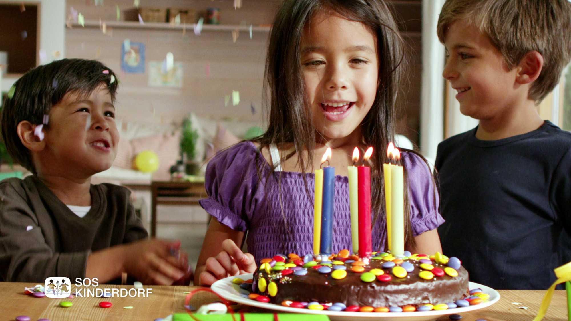 Das Bild zeigt drei Kinder, zwei Jungs und ein Mädchen. Das Mädchen steht zwischen den beiden Jungs. sie stehen vor einem Tisch, im Hintergrund sieht man eine Küche. Auf dem Tisch steht eine Kuchen, auf diesem stehen Kerzen. Die Jungs werfen Konfetti in die Luft das Mädchen möchte die Kerzen ausblasen. In der linken Ecke des Bildes sieht man das SOS Kinderdorflogo sowie die Worte SOS Kinderdorf. Das Bild dient als Sliderbild für den Portfolioeintrag SOS-Kinderdorf Sommer von Panda Pictures.