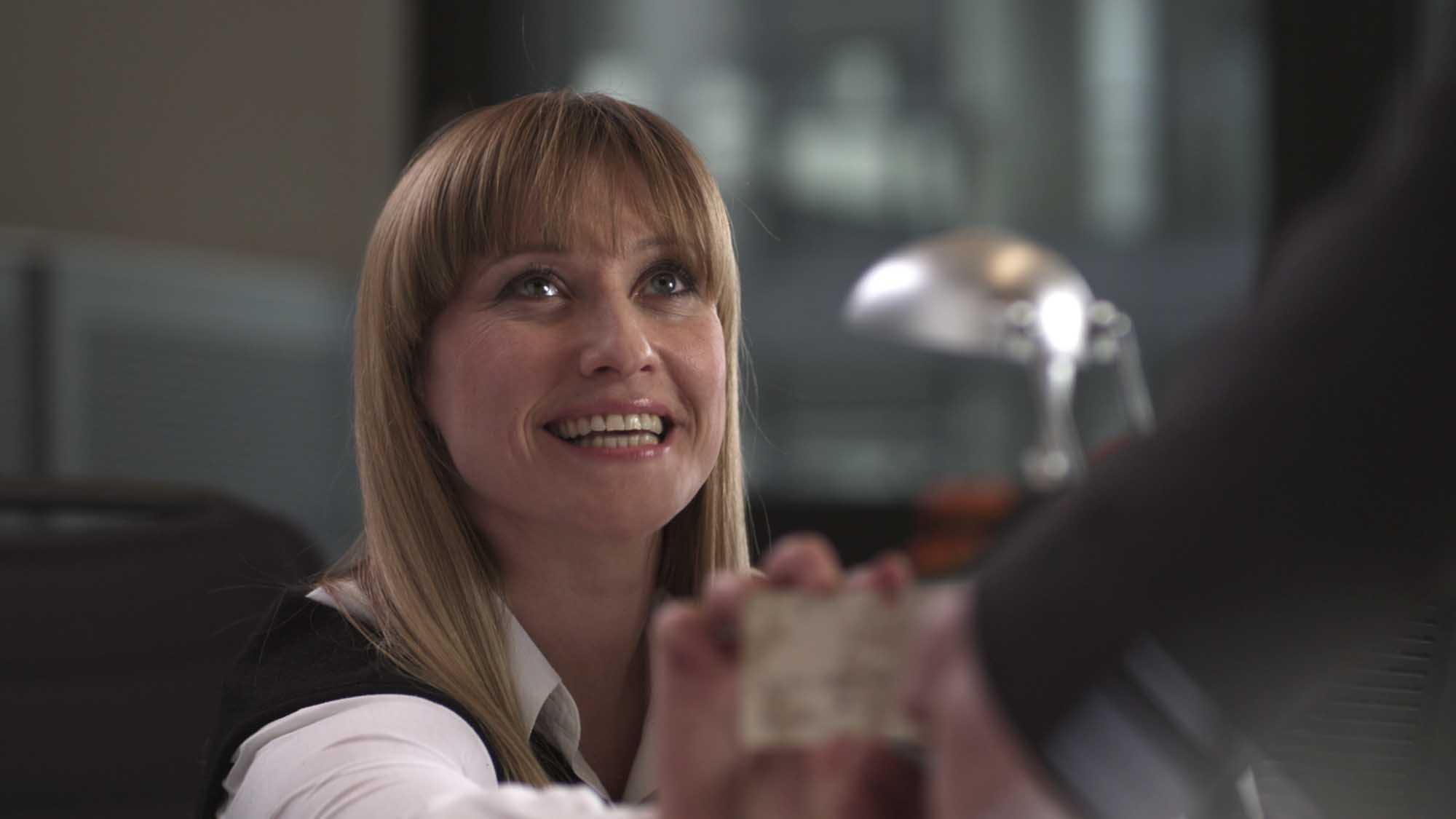 Das Bild zeigt eine blonde, lachende Frau. Sie hält eine Kreditkarte in der Hand demonstrativ nach vorne. Sie trägt ein weißes Hemd mit einem schwarzen Überzug. Vor ihr sieht man einen verschwommenen Arm. Das Bild dient als Sliderbild für den Portfolioeintrag Mastercard mc-bizz von Panda Pictures.