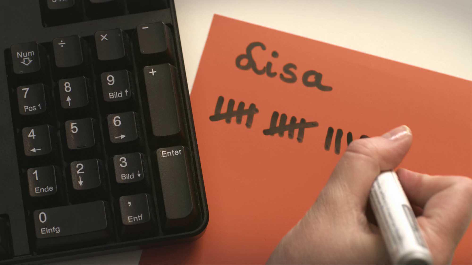 Das Bild zeigt eine orangene Karte auf der das Wort Lisa steht. Darunter sieht man eine Strichliste neben der auf der rechten Seite ein hand liegt die einen Stift in der Hand hält. Links sieht man einen Teil einer Tastatur. Das Bild dient als Sliderbild für den Portfolioeintrag Mastercard mc-bizz von Panda Pictures.