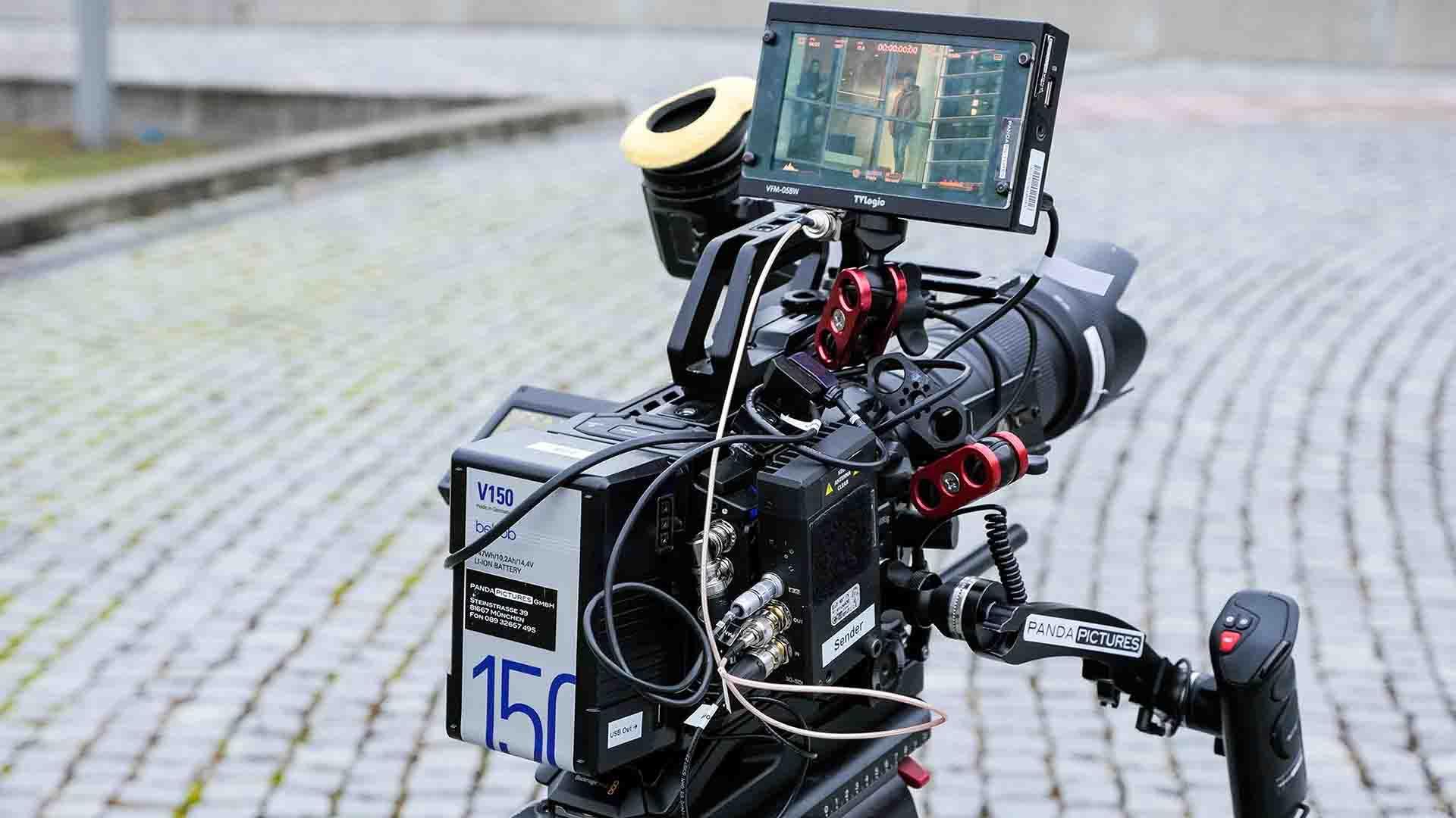 """Das Bild zeigt eine schwarze Kamera. Diese steht auf einem Boden, der gepflastert ist. Ein Monitor ist an der Kamera angebracht. Auf dem Monitor ist eine Szene zu sehen, die gefilmt wird. Das Bild dient als Sliderbild für den Portfolioeintrag """"Alphabet AlphaElectric Erklärfilm"""" von Panda Pictures."""
