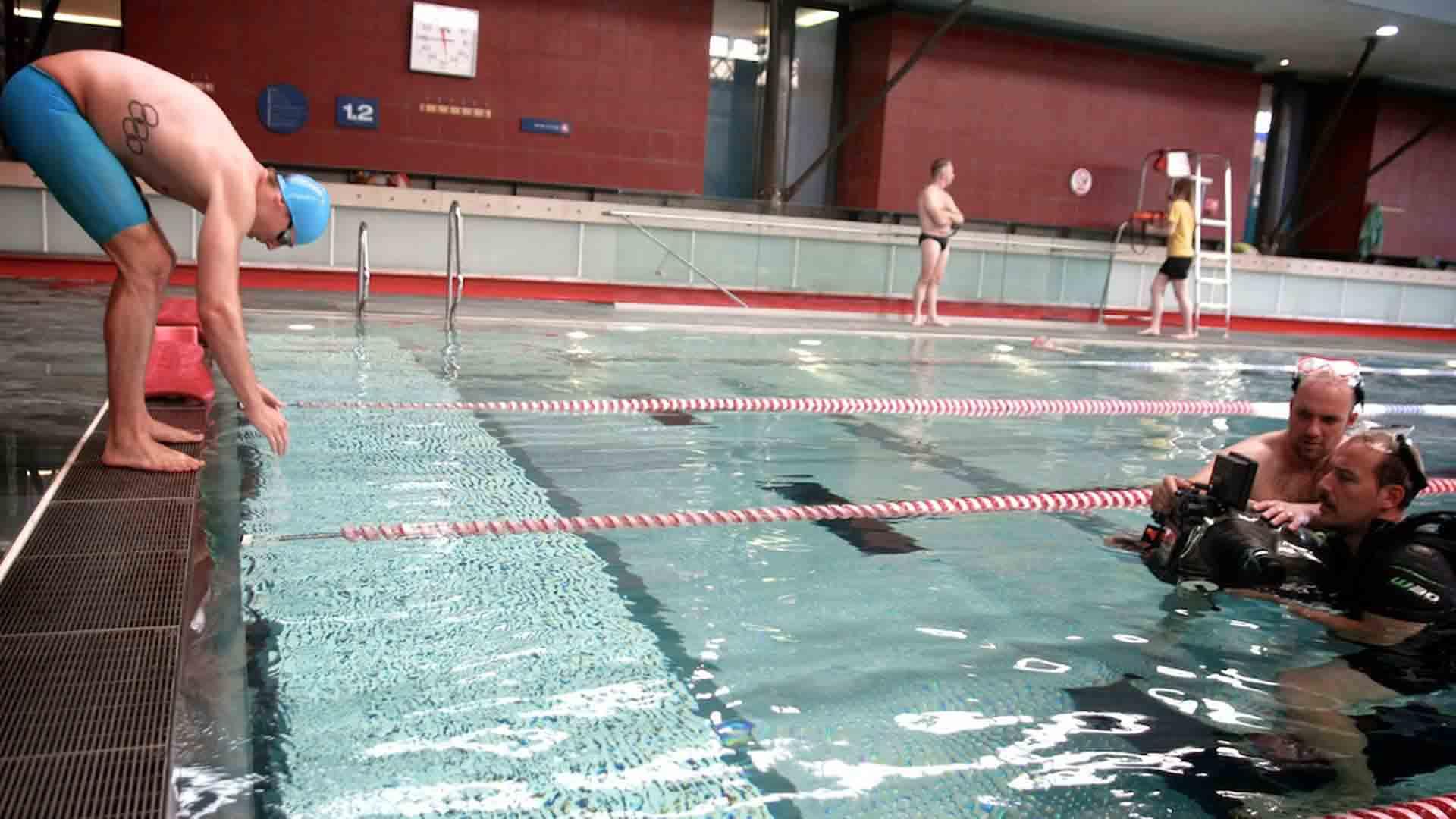 Das Bild zeigt ein Schwimmbecken in einem Schwimmbad. Am Beckenrand steht ein Mann in blauer Badehose. Auf seinen Rippen ist ein Tattoo, dass die Olympiaringe abbildet. Vor ihm im Wasser stehen zwei Männer. Sie filmen ihn. Einer von den beiden trägt einen Taucheranzug. Am Beckengrand im Hintergrund stehen zwei Männer, man erkennt sie jedoch nicht. Das Bild dient als Sliderbild für den Portfolioeintrag Speedo – Marketing- und PR-Film von Panda Pictures.