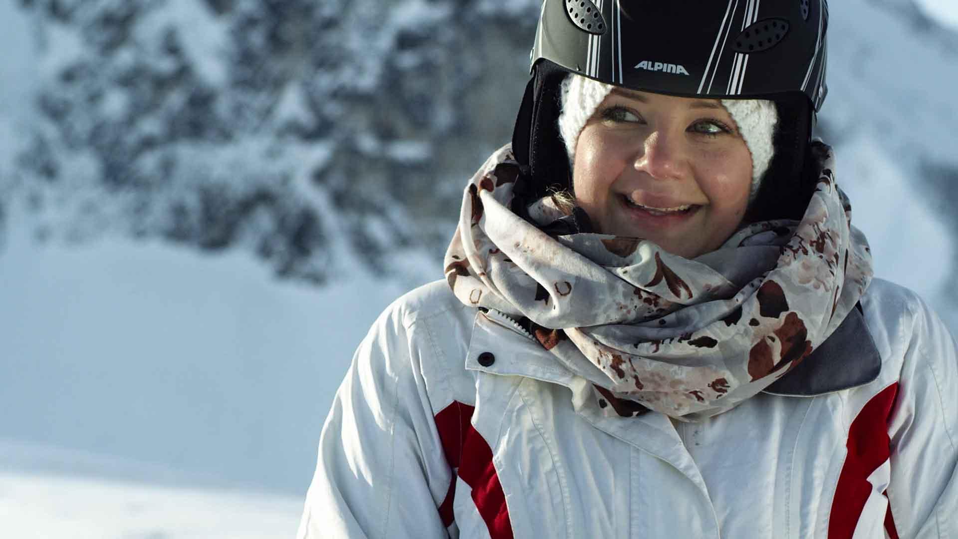Das Bild zeigt eine Frau die sich auf der rechten Seite des Bildes befindet. Sie trägt Skikleidung und einen Helm in der Farbe schwarz. Hinter ihr sieht man einen Berg. Das Bild dient als Sliderbild für den Portfolioientrag Bayerntourismus Wintercamping in Bayern von Panda Pictures.