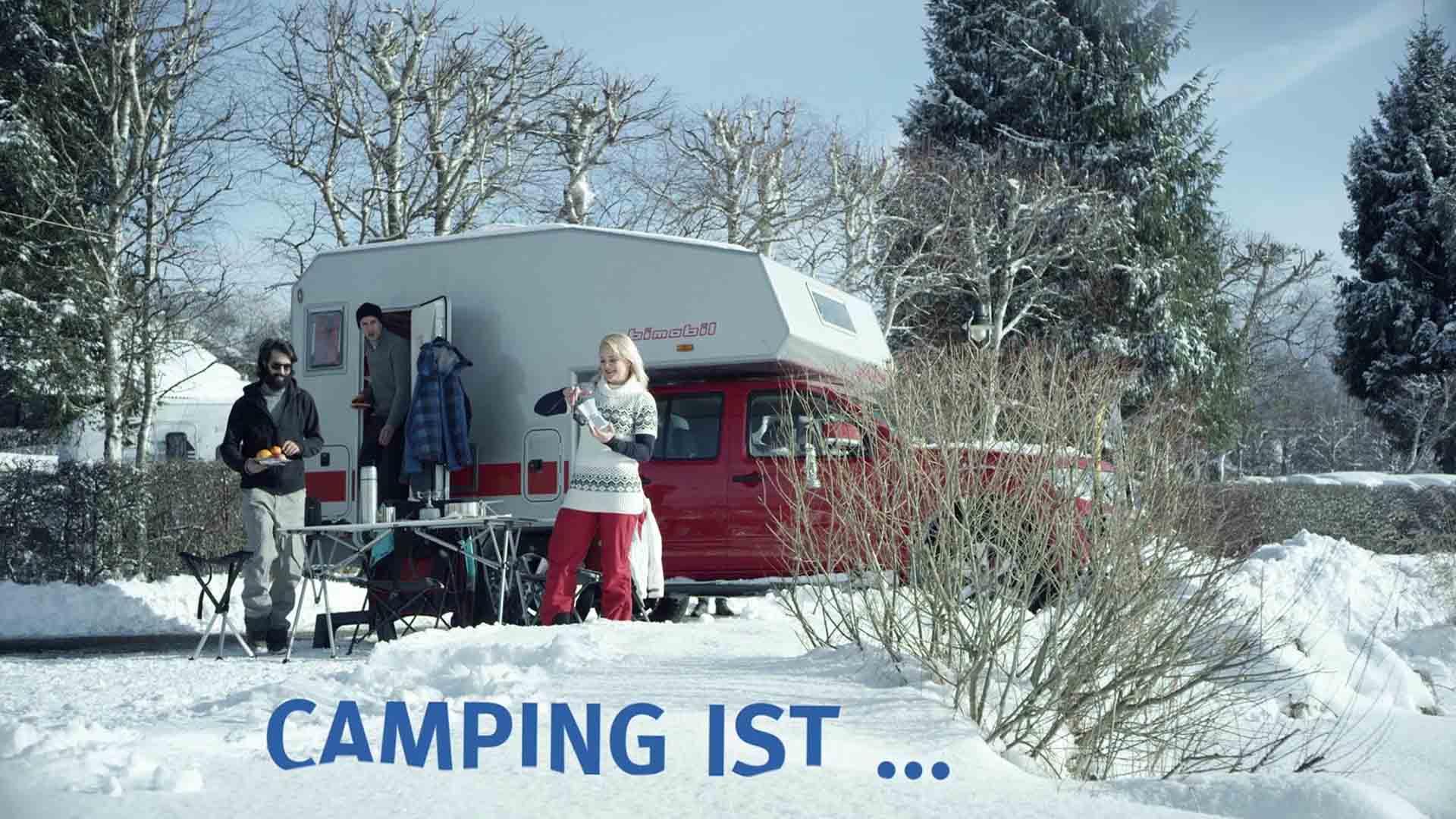 """Das Bild zeigt einen roten Camper. Er steht in einer verschneiten Landschaft. Vor ihm stehen Menschen. Sie campen. Darunter sieht man die Worte """"Campen ist.."""" Sie wurden per Animation eingefügt. Das Bild dient als Sliderbild für den Portfolioeintrag Bayerntourismus Wintercamping in Bayern von Panda Pictures."""