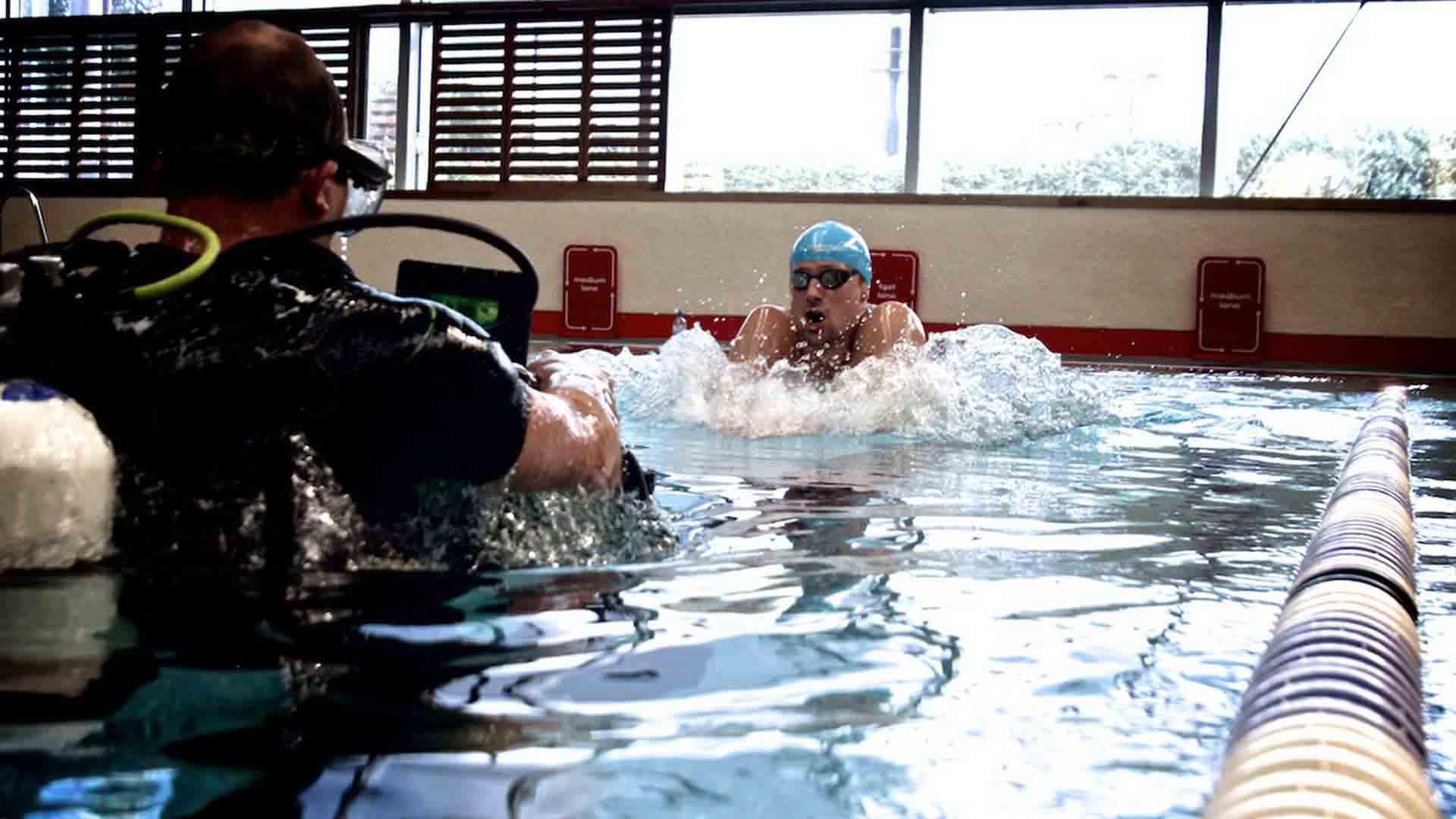 Das Bild zeigt einen Schwimmer, der in einem Schwimmbecken ist. Er ist gerade dabei unter Wasser zu tauchen. Er trägt eine blaue Badekappe auf dem Kopf. Vor ihm, mit in der Schwimmbahn, befindet sich ein Kameramann. Er trägt eine Taucherausrüstung und eine Kamera in der Hand mit der er den Schwimmer filmt. Das ganze findet in einem Hallenbad statt. Das Bild dient als Sliderbild für den Portfolioeintrag Speedo – Marketing- und PR-Film von Panda Pictures.