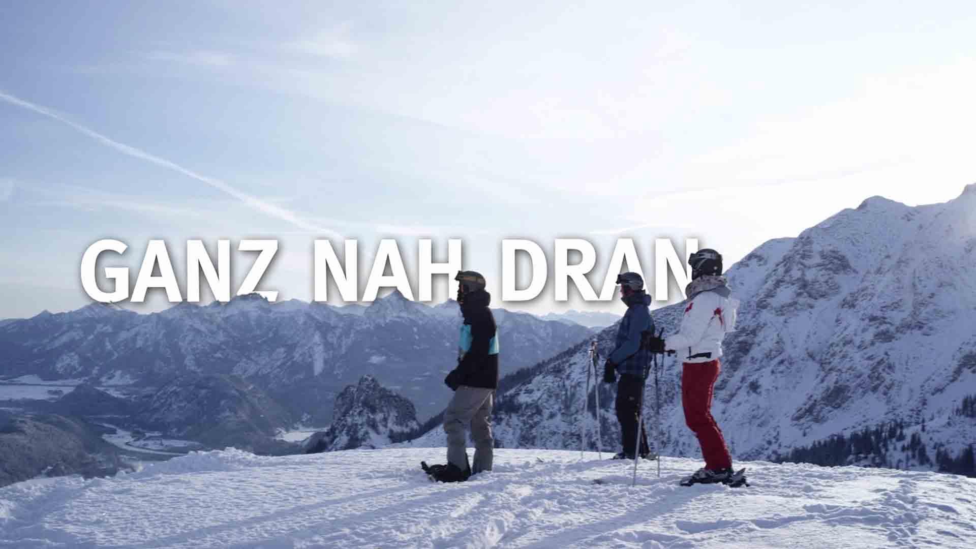 Das Bild zeigt Menschen. Sie stehen auf einem Berg. Sie tragen Winterkleidung. Sie fahren Ski. Sie stehen vor einem Berg und in der Luft ragen die Worte Ganz Nah dran, die per Animation eingefügt wurden. Das Bild dient als Sliderbild für den Portfolioeintrag Bayerntourismus Wintercamping in Bayern von Panda Pictures.