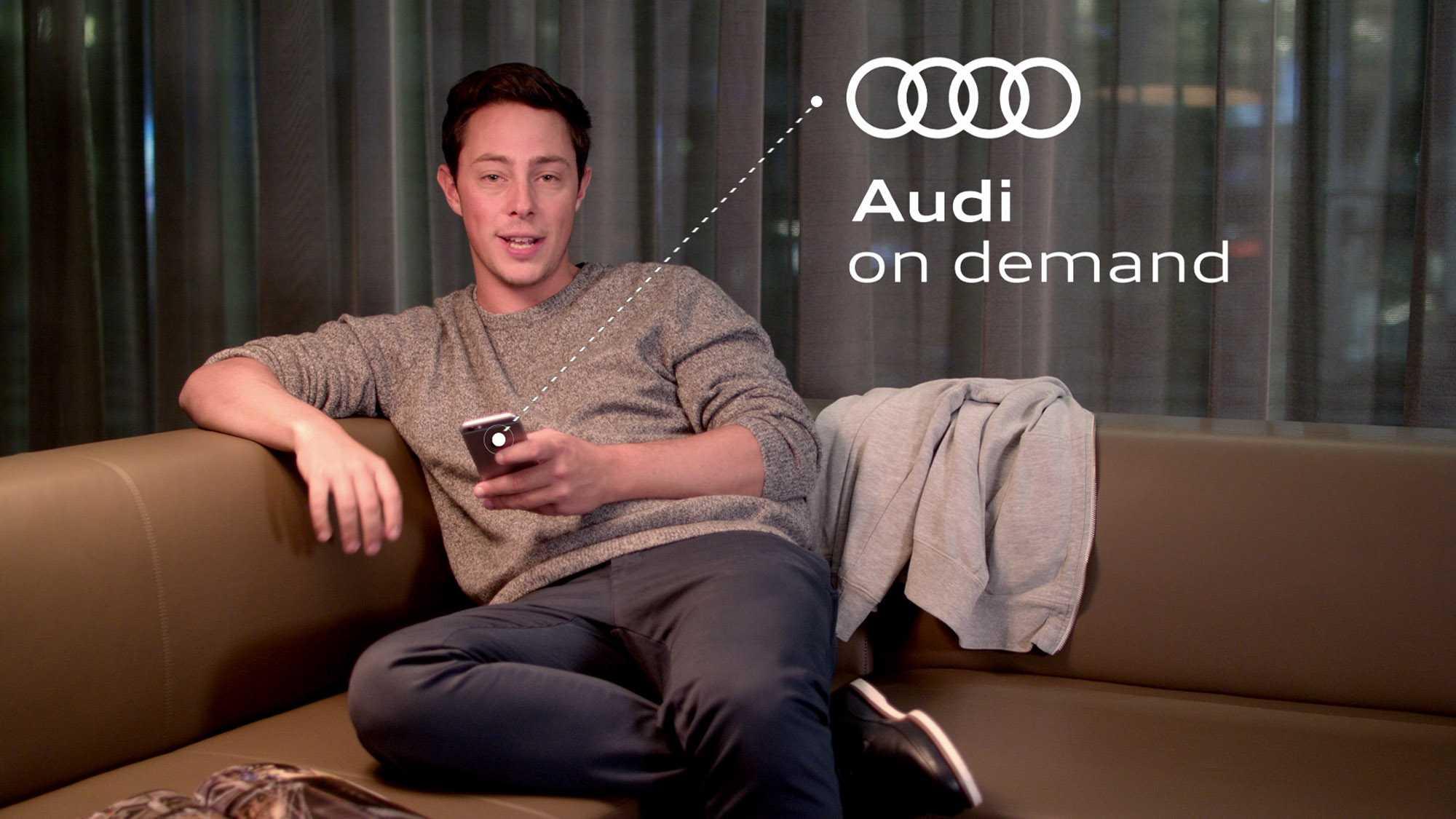 """Das Bild zeigt einen Moderator. Sein Name ist Ben Constanduros. Er befindet sich sitzend auf einem beigen Sofa. Hinter ihm sind graue Vorhänge angebracht. In seiner rechten Hand hält er ein Handy. Von diesem geht eine Linie aus, welche gestrichelt ist. An dieser Linie ist ein Text angebracht. Dieser Zeigt die Worte """"Audi on demand"""". Ebenfalls ist das Audi Logo zu sehen. Das Bild dient als Making Of Bild für den Portfolioeintrag Audi on demand – Launchfilm von Panda Pictures."""