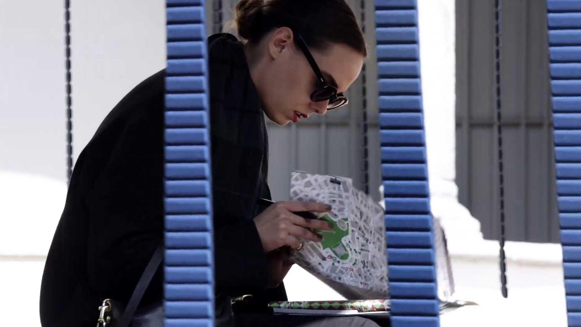 Das Bild zeigt eine sitzende Frau. Sie hält eine Stadtkarte in ihrer Hand. Sie trägt eine schwarze Sonnenbrille und schwarze Kleidung. Ihr Blick ist auf die Karte gerichtet. Im Vordergrund sind blaue Streifen, die durch das Bild laufen, zu sehen. Das Bild dient als Making Of Bild für den Portfolioeintrag BMW Quiet Motion von Panda Pictures.