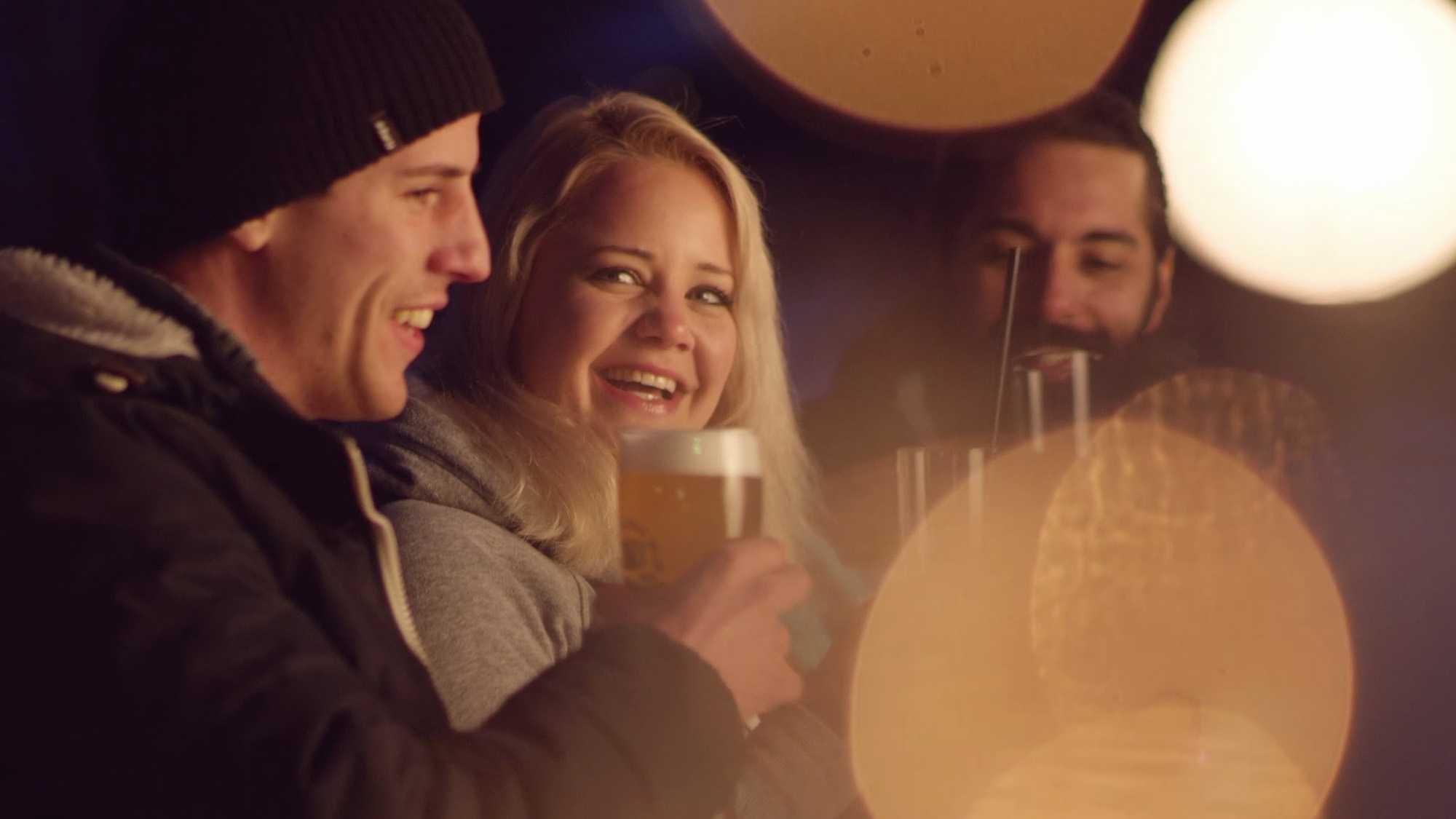 Das Bild zeigt eine Gruppe von Menschen. Zwei Männer sitzen neben einer Frau. Sie stoßen alle gegenseitig mit Bier an. Über dem Bild sieht man einzelne Lichtpunkte. Das Bild dient als Making Of Bild für den Portfolioeintrag Bayerntourismus Wintercamping in Bayern von Panda Picutres.