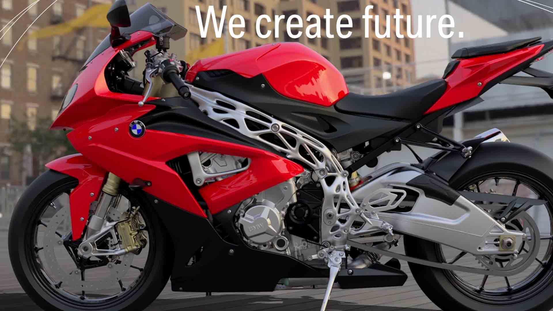 """Das Bild zeigt ein Motorrad der Farbe rot. Über dem Motorrad ist ein animierter Text zu sehen. Er sagt """"We create future."""" Das Motorrad wird von der Seite gezeigt. Das Bild dient als Making Of Bild für den Portfolioeintrag BMW Group – 3D Druck/Additive Manufacturing Campus von Panda Pictures."""