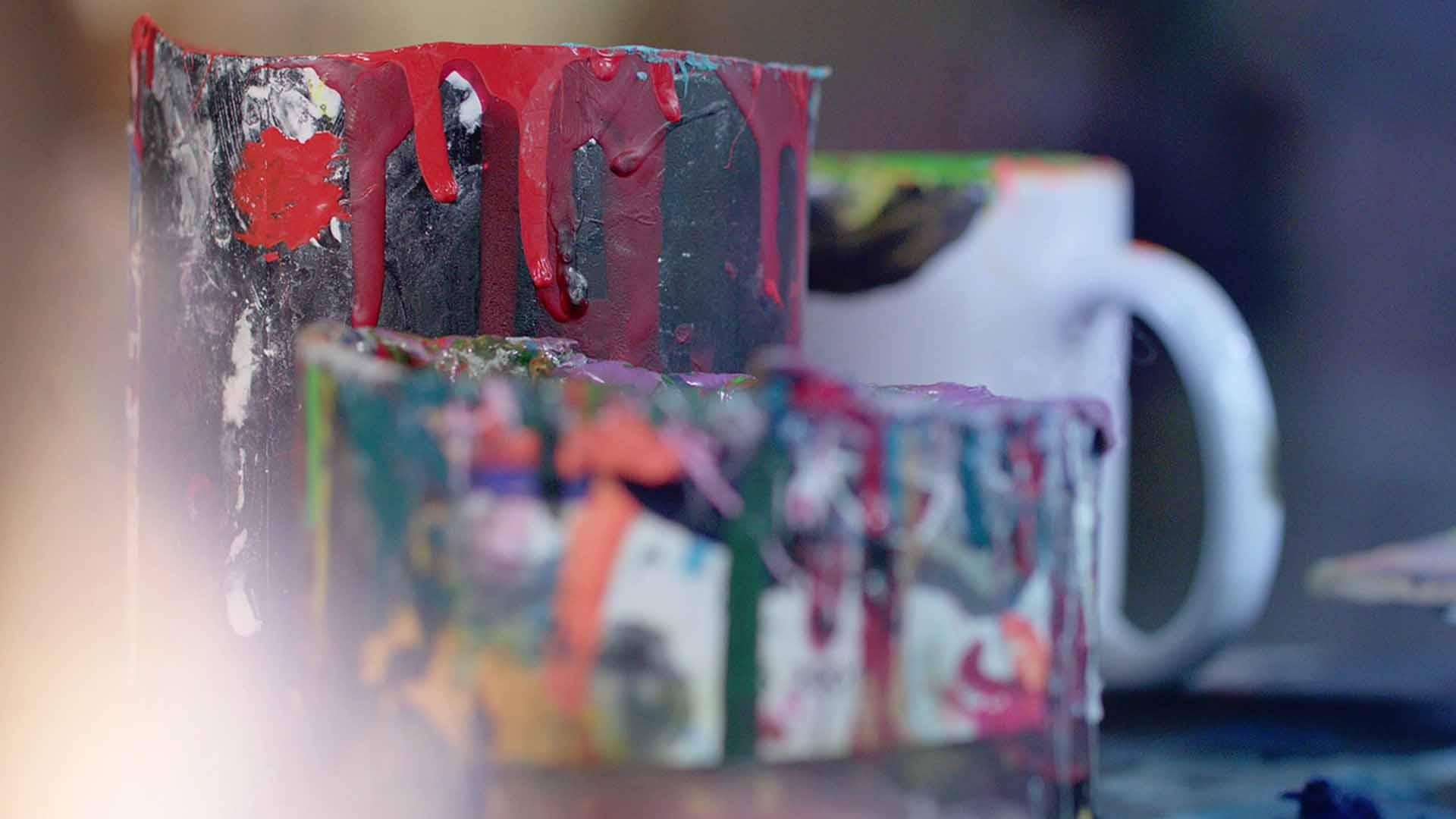 Das Bild zeigt einen Farbbecher. In diesem wurden verschiedene Farben gemischt. Tropfen aus Farben laufen an ihm herunter. Das Bild dient als Making Of Bild für den Portfolioeintrag BMW Plant San Luis Potosí Mexico von Panda Pictures.
