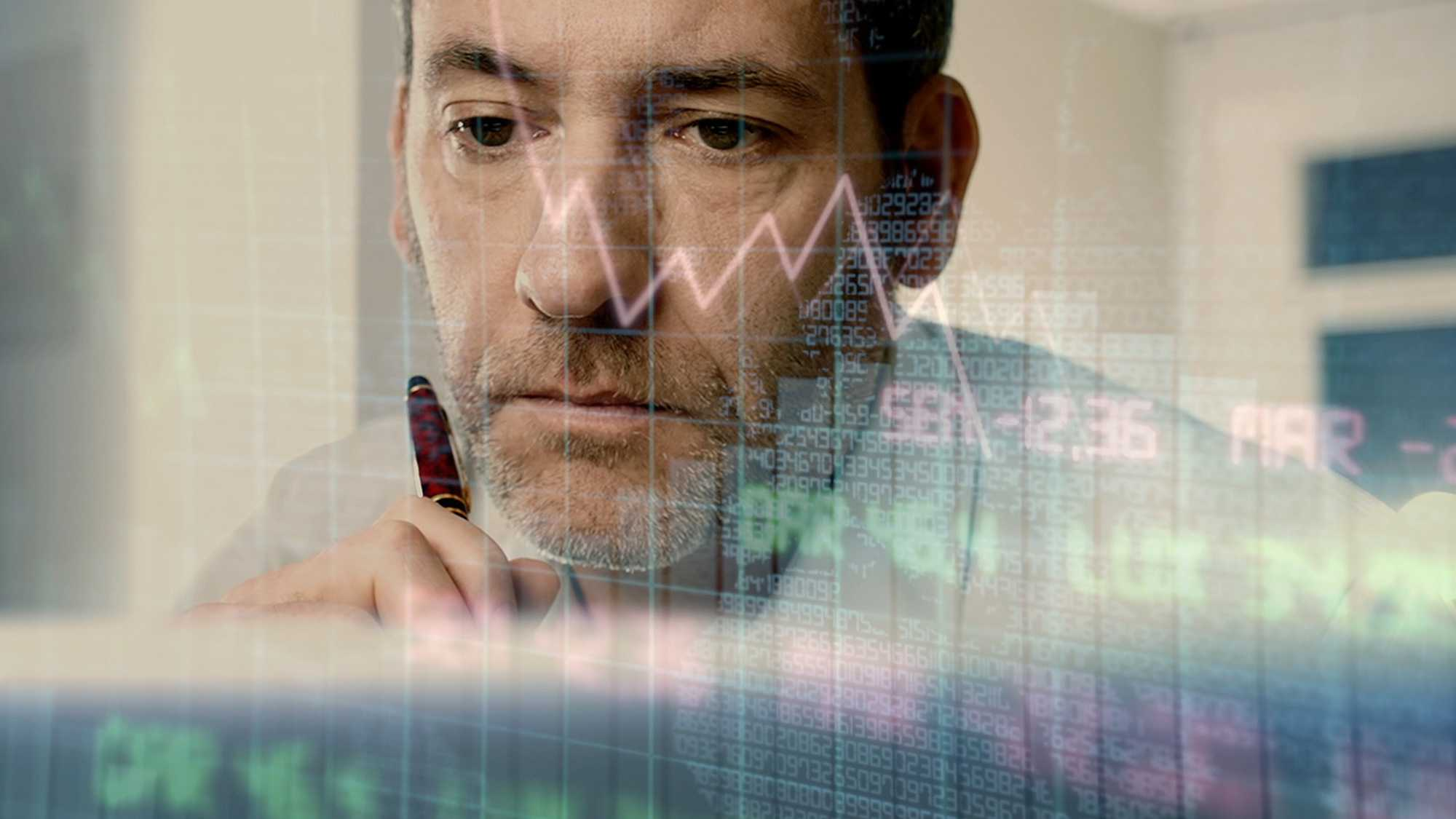 Das Bild zeigt die Sicht auf einen Mann aus einem Bildschirm heraus. Über ihm sieht man den Bildschirminhalt. Man sieht Börsenwerte. Er schaut in den Bildschirm und hält einen Stift in seiner Hand. Das Bild dient als Making Of Bild für den Portfolioeintrag H1 Fond von Panda Pictures.