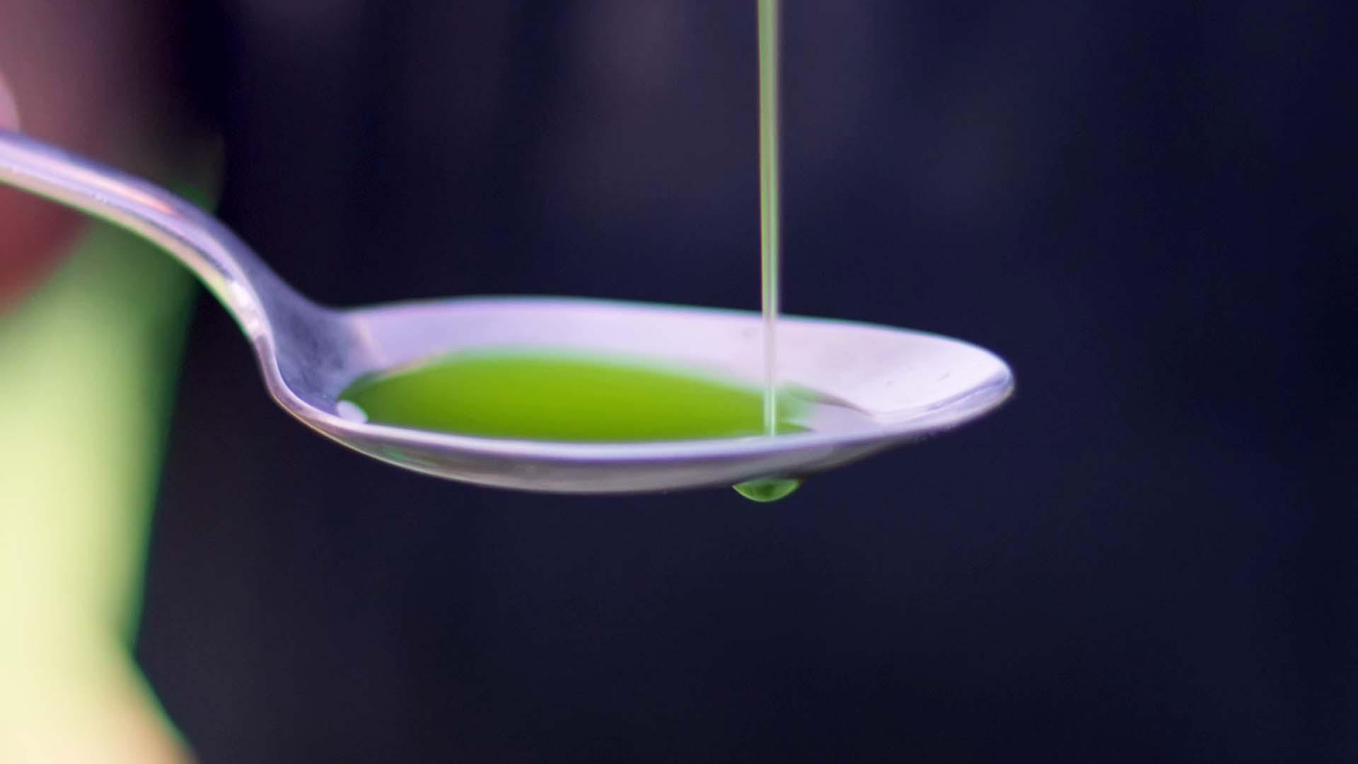 Das Bild zeigt einen Löffel. Dieser Löffel hat die Farbe silber. Auf ihn läuft ein grünes Öl. Das Bild dient als Making Of Bild für den Portfolioeintrag Kurzfilm Tränen der Olive von Panda Pictures.