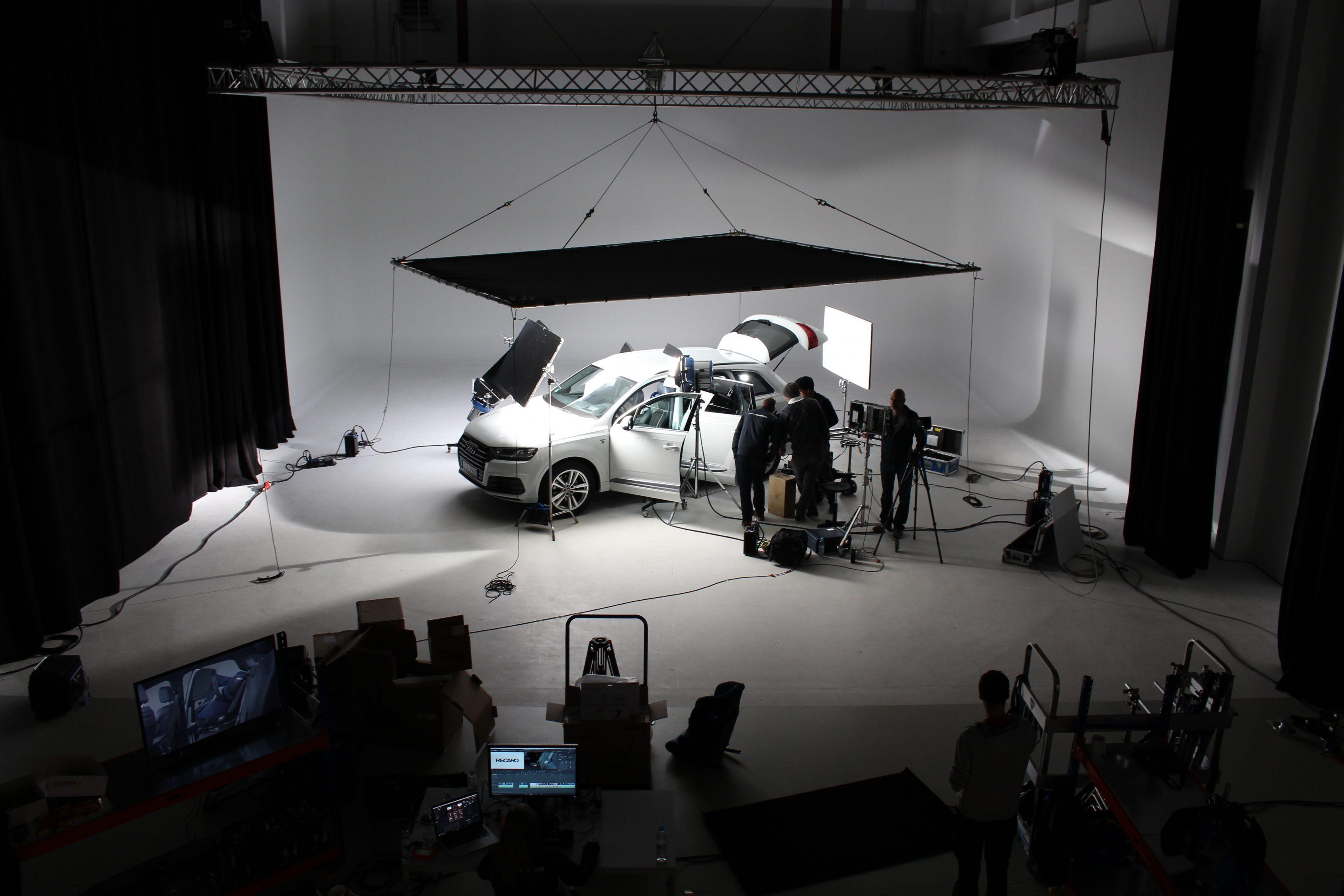 Das Bild zeigt einen Raum. In diesem wird gefilmt. Man sieht auf einer weißen Leinwand ein Auto stehen. Über diesem ist eine schwarze Platte angebracht. Das Auto ist beleuchtet, der Hintergrund ist schwarz und man sieht dort Silhouetten von Menschen stehen. Sie tragen Kameras und filmen das ganze. Das Bild dient als Making Of Bild für den Portfolioeintrag RECARO Child Safety – Einbaufilme von Panda Pictures.