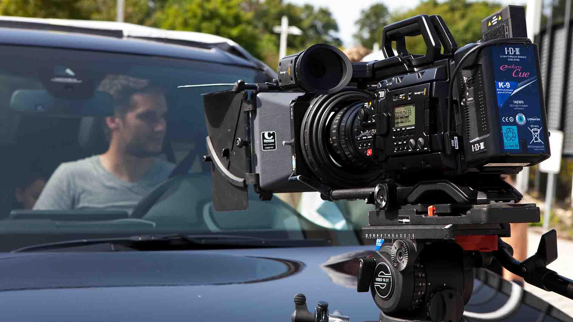 Das Bild zeigt eine Kamera. Diese Kamera ist auf ein Auto gerichtet. Das Auto ist schwarz sowie die Kamera auch. Auf dem Fahrersitz des Wagens sitzt ein Mann. Das Bild dient als Making Of Bild für den Portfolioeintrag RECARO Child Safety – Childseats Save Lives von Panda Pictures.