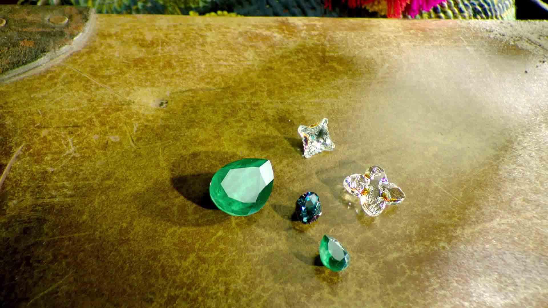 Zu sehen sind fünf Edelsteine. Sie liegen auf einem braunen Hintergrund. Auf der linken Seite liegen drei Edelsteine. Sie sind grün. Auf der rechten Seite liegen zwei Edelsteine. Diese sind transparent. Das Bild dient als Making Of Bild für den Portfolioeintrag Swarovski Produktfilm von Panda Pictures.