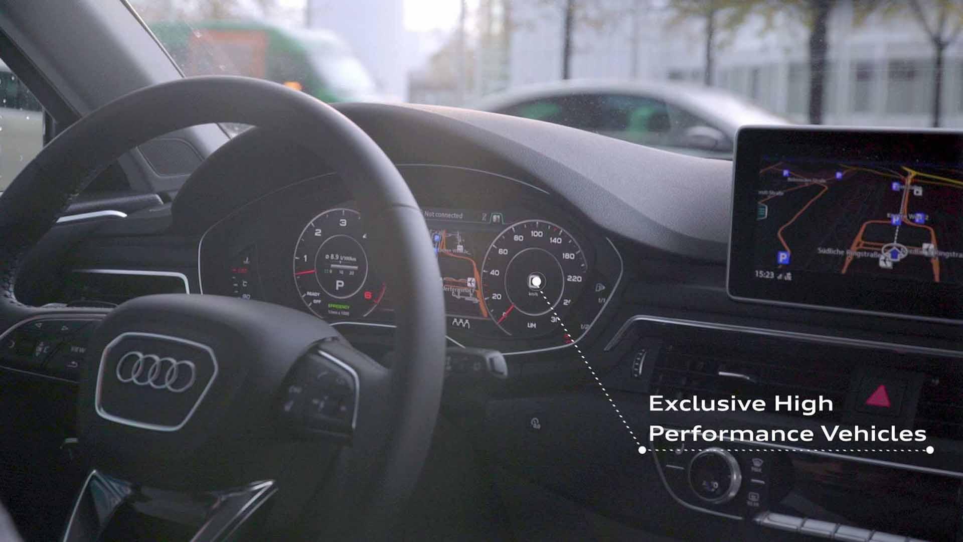"""Das Bild zeigt den Innenraum eines Fahrzeugs. Man sieht das Cockpit. Es ist grau. Die Armaturen sowie das Lenkrad sind zu sehen. Ein kleiner Bildschirm zeigt ein Navigationssystem laufen. Eine gestrichelte Linie geht von dem Tacho ab. An ihm sind die Worte """"Exclusive high performance vehicles"""" angebracht. Das Bild dient als Sliderbild für den Portfolioeintrag Audi on demand – Launchfilm von Panda Pictures."""