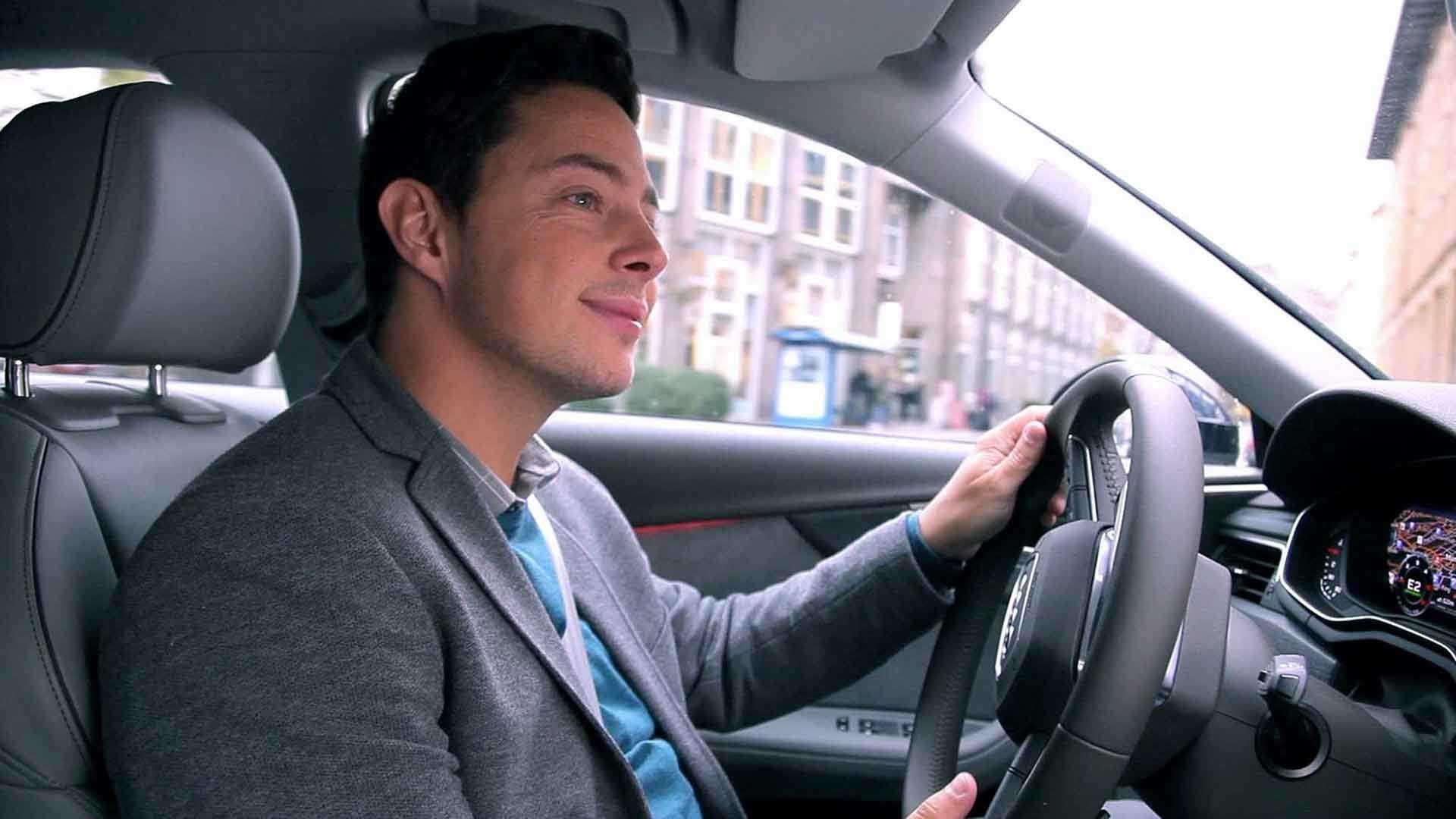 Das Bild zeigt den Moderator Ben Constanduros. Er sitzt in einem Audi, was man an dem Logo auf dem Lenkrad erkennen kann. Er hält dieses Lenkrad in seiner linken Hand. Er lächelt. Das Bild dient als Sliderbild für den Portfolioeintrag Audi on demand – Launchfilm von Panda Pictures.