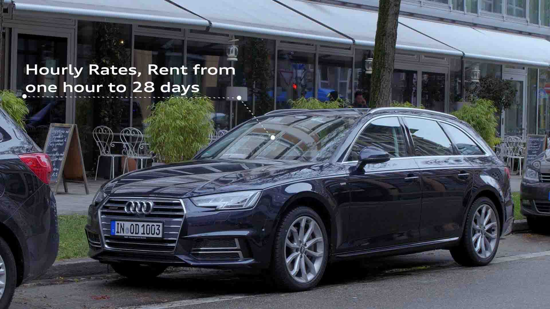 """Das Bild zeigt einen parkenden Audi. Er ist schwarz und steht vor einem Restaurant. Vor diesem Restaurant stehen weiße Stühle und eine kleine, schwarze Menükarte. Eine Linie, die gestrichelt ist, führt von dem Auto ab. An ihr sind die Worte steht """"Hourly Rates, rent from one hour to 28 days"""" angebracht. Das Bild dient als Sliderbild für den Portfolioeintrag Audi on demand – Launchfilm von Panda Pictures."""