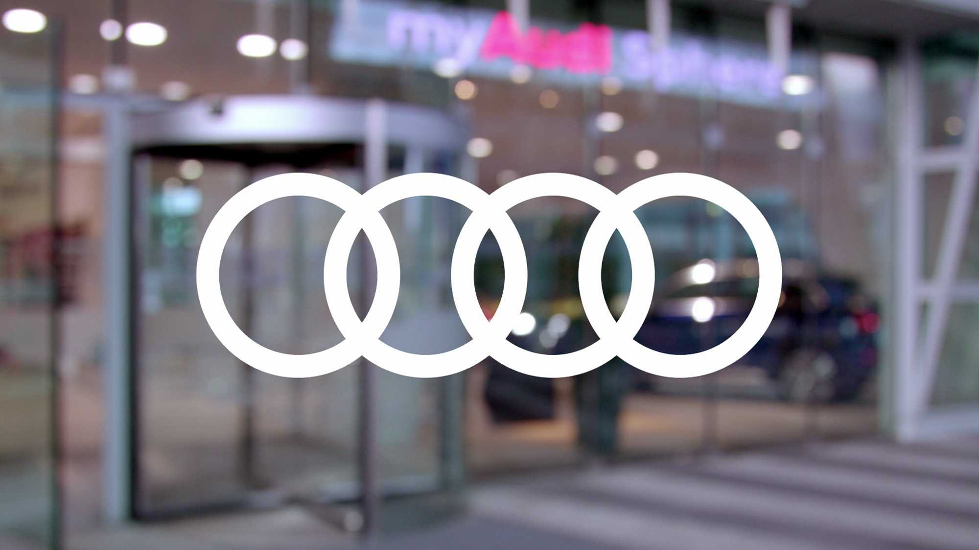 Wir sehen das Logo von Audi. Es ist in der Farbe weiß auf einen verschwommenen Hintergrund angebracht. Der Hintergrund zeigt den Eingang einer Audi Geschäftsstelle. Das Bild dient als Sliderbild für den Portfolioeintrag Audi on demand – Launchfilm von Panda Pictures.