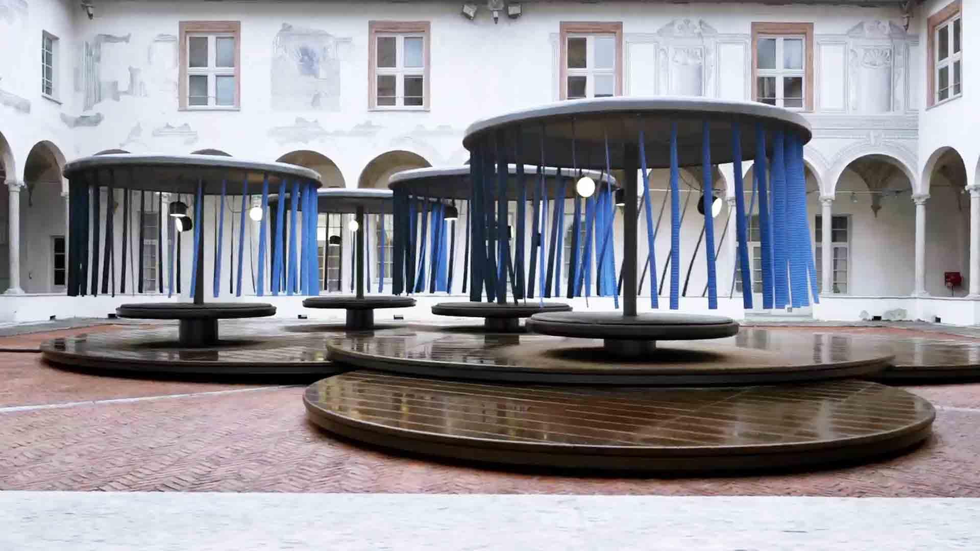 """Das Bild zeigt vier Gebilde. Sie erinnern an ein Karussell. Sie stehen auf runden Holzscheiben in einem Innenhof. Dieser Innenhof gehört zu einem großen, weißen Haus. Im Hintergrund sieht man die Fenster des Hauses. Auf der unteren Ebene sind Bögen in das Haus eingefügt. Von den Decken des Karussells hängen blaue Streifen. Das Bild dient als Sliderbild für den Portfolioeintrag """"BMW Quiet Motion"""" von Panda Pictures."""