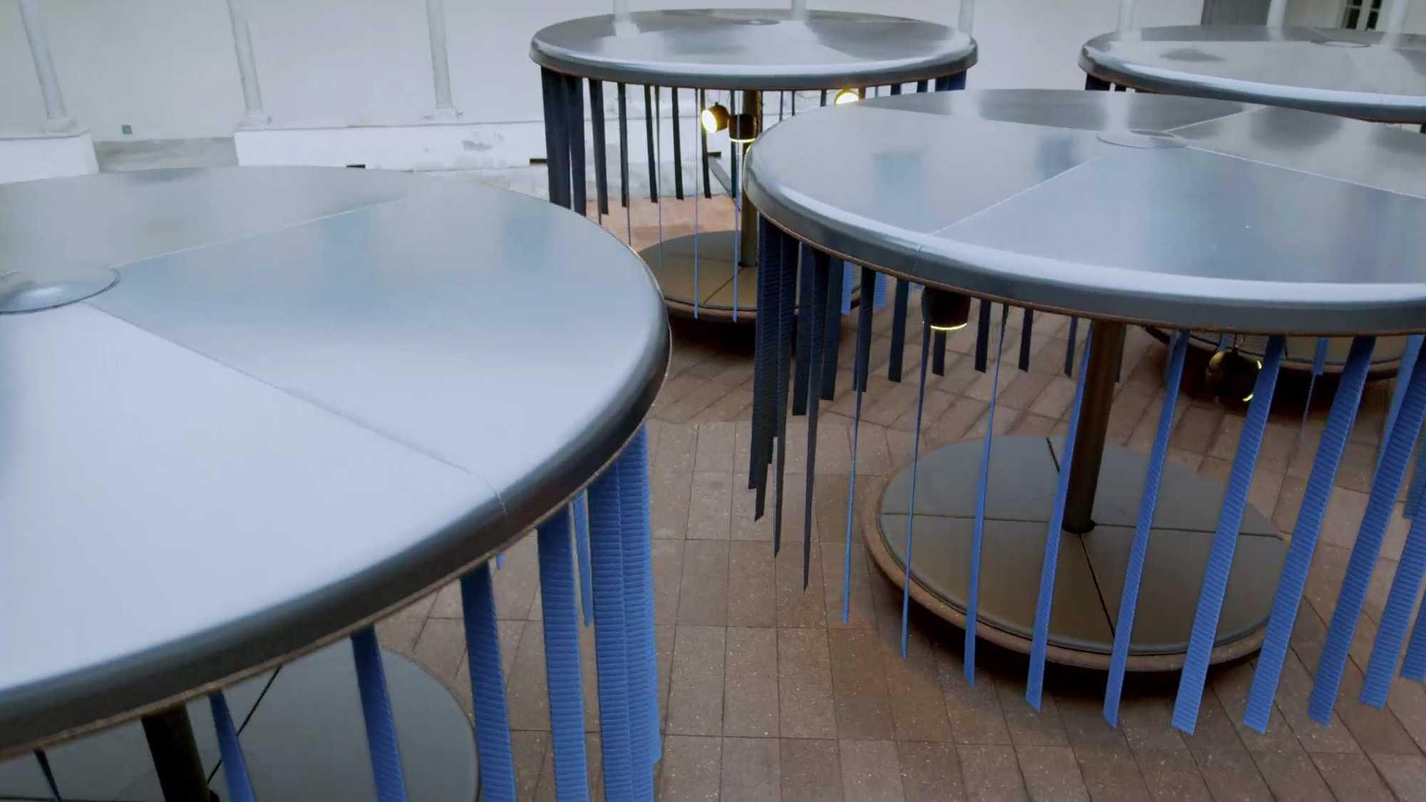 Zu sehen sind verschiedene Installationen. Sie erinnern an ein Karussell. Von den Decken dieser Installationen hängen blaue Streifen. Sie stehen auf einem Untergrund aus braunem Stein. Das Bild dient als Sliderbild für den Portfolioeintrag BMW Quiet Motion von Panda Pictures.