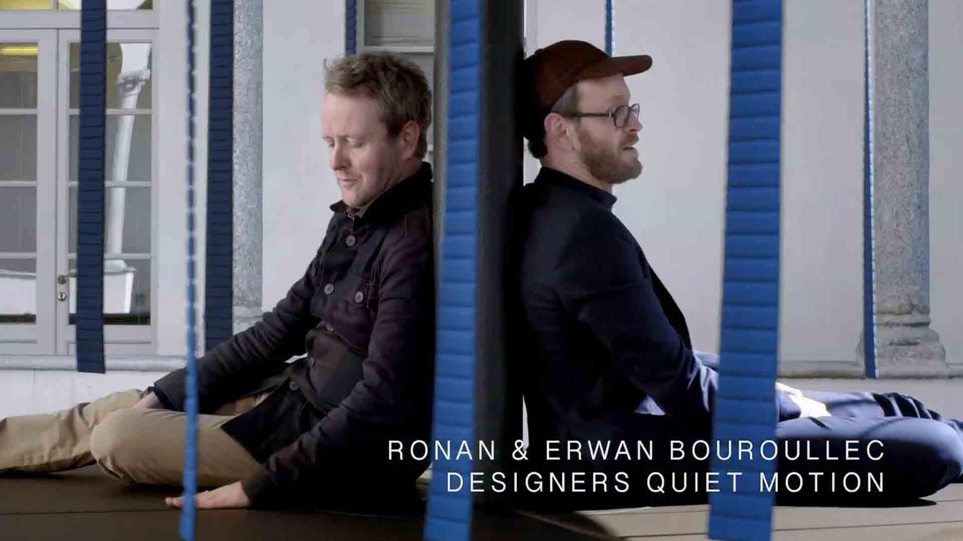 """Das Bild zeigt zwei Männer, die Rücken an Rücken zueinander sitzen. Der Mann, der auf der rechten Seite sitzt, trägt eine Mütze. Vor den beiden sieht man blaue Streifen durch das Bild wehen. Die rechte Seite des Bildes zeigt die eingebetteten, animierten Namen der beiden. Zu lesen ist """"Ronan & Erwan Bouroullec Designer Quiet Motion"""". Das Bild dient als Sliderbild für den Portfolioeintrag """"BMW Quiet Motion"""" von Panda Pictures."""