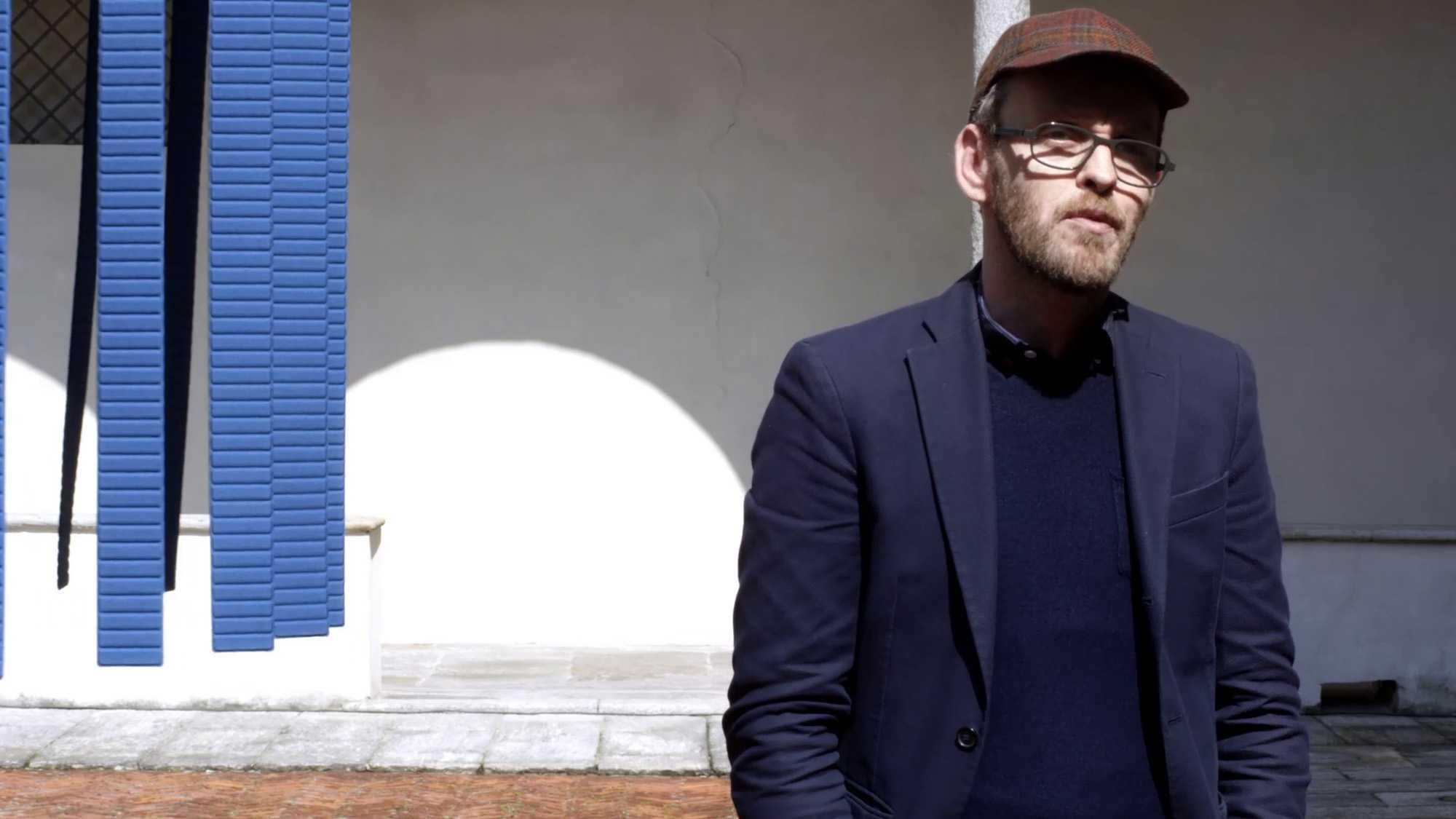 Das Bild zeigt einen Mann der vor einer weißen Wand steht. Links an dieser Wand sind blaue Streifen zu sehen. Das Bild dient als Sliderbild für den Portfolioeintrag BMW Quiet Motion von Panda Pictures.