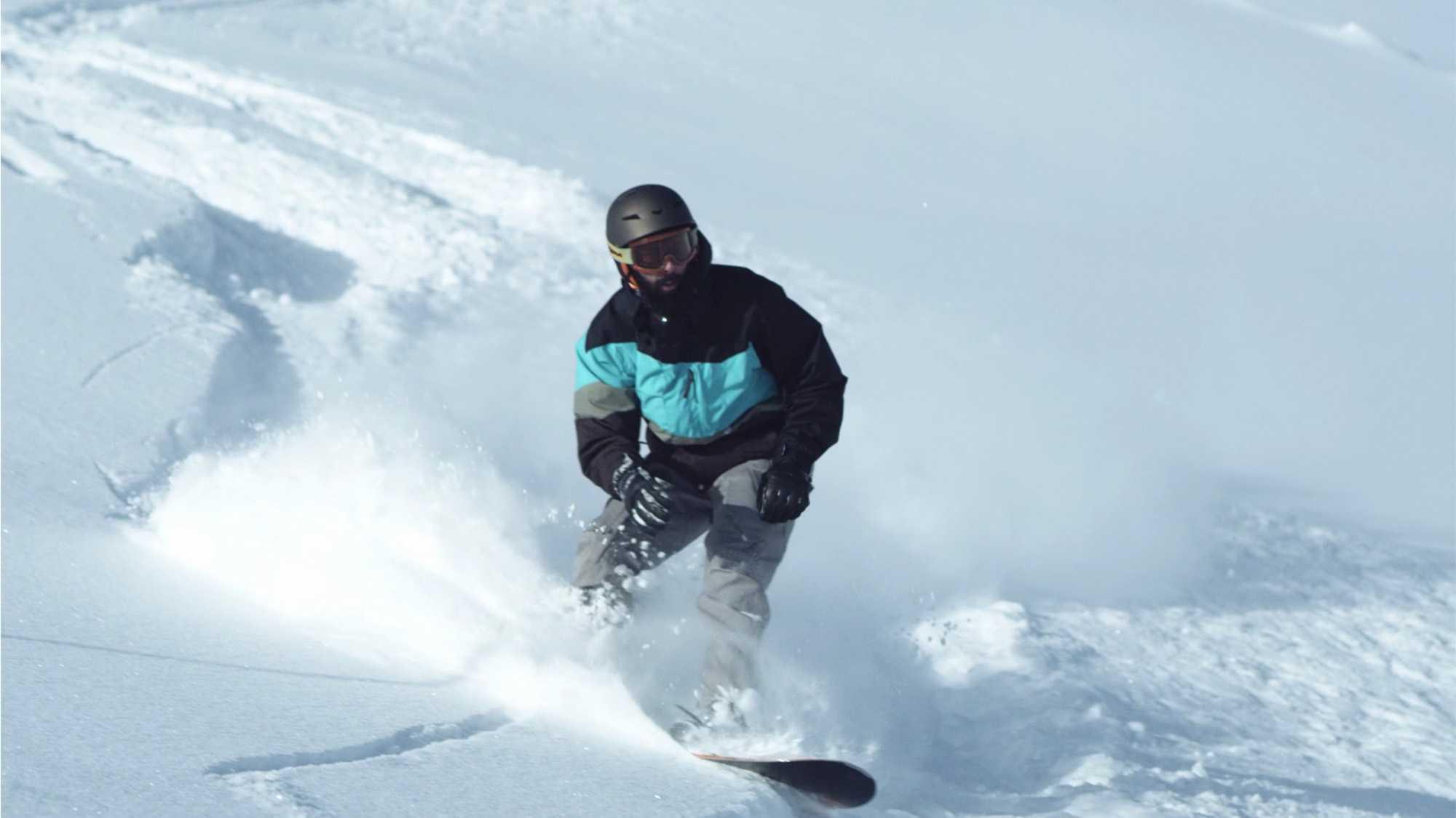 Das Bild zeigt einen Snowboarder. Er fährt durch den Schnee. Man erkennt den Fahrer nicht, da sein Gesicht verdeckt ist. Das Bild dient als Sliderbild für den Portfolioeintrag Bayerntourismus Wintercamping in Bayern von Panda Pictures.