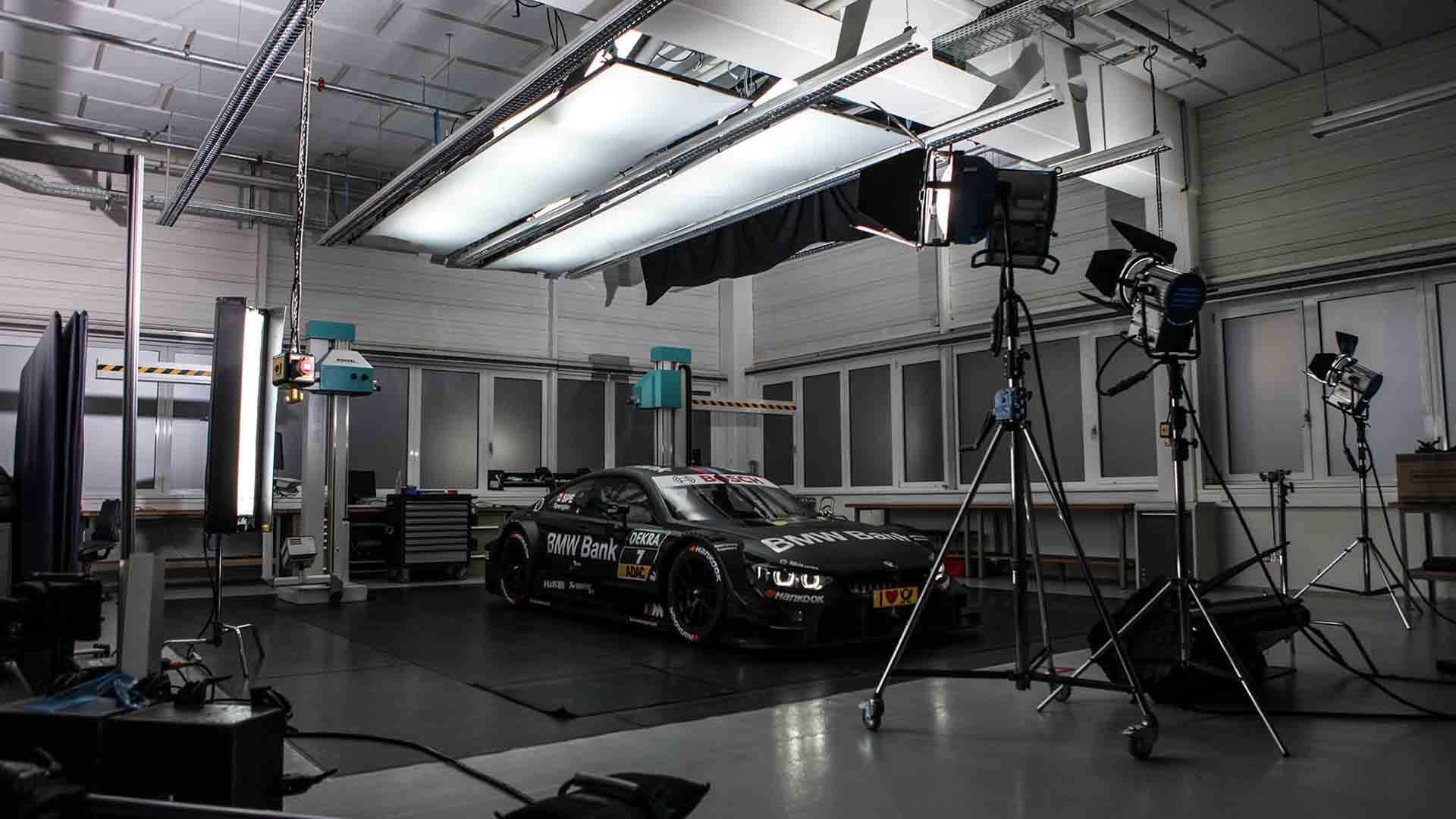 Zu sehen ist ein schwarzer Rennwagen von BMW. Er steht in der Mitte eines Raumes. Um ihn herum stehen Kameras, die ihn filmen. Über ihm hängen große Lichter. Das Bild dient als Sliderbild für den Portfolioeintrag BMW Bank Financial Services – Bruno Spengler von Panda Pictures.