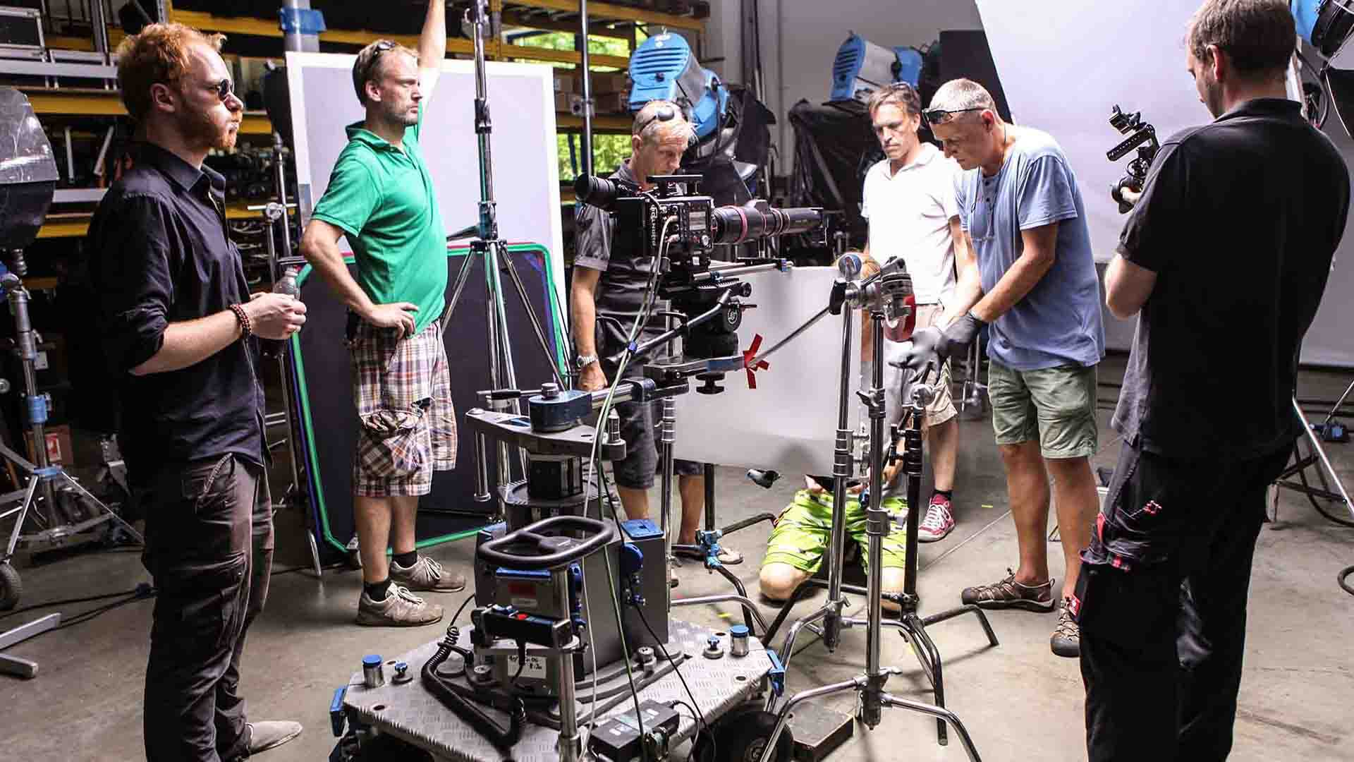Das Bild zeigt einen Kreis aus Männern. Es sind sechs Stück insgesamt. Sie stehen um verschiedenes Kamerazubehör herum. Ein Mann, der auf der rechten Seite steht, filmt. Das Bild dient als Sliderbild für den Portfolioeintrag BMW / MINI Engine Oil Highspeed von Panda Pictures.