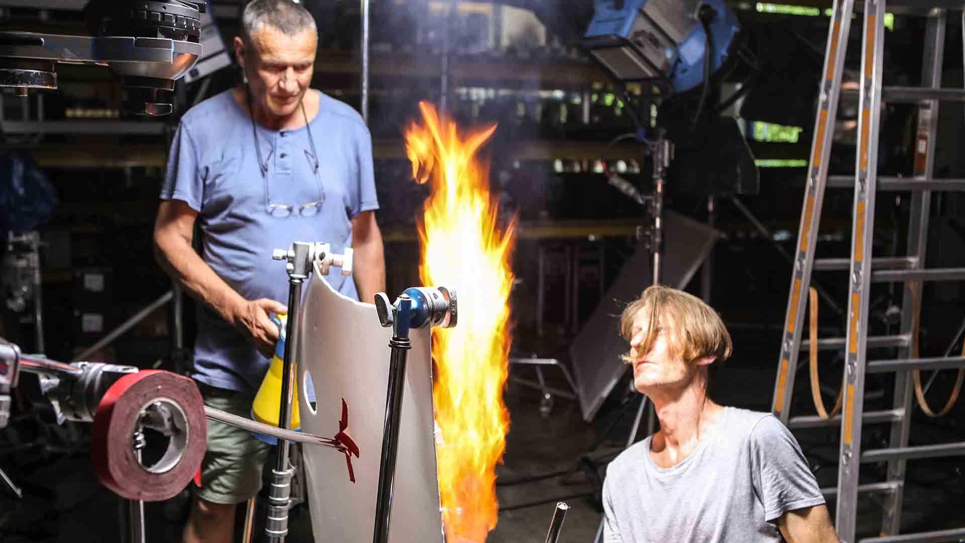 Das Bild zeigt zwei Männer, die sich vor einer Flamme befinden. Auf der linken Seite steht ein Mann vor der Flamme, auf der rechten Seite kniet ein Mann vor der Flamme. Vor der Flamme ist ein Banner angebracht. Das ganze befindet sich in einer Werkstatt. Das Bild dient als Sliderbild für den Portfolioeintrag BMW / MINI Engine Oil Highspeed von Panda Pictures.