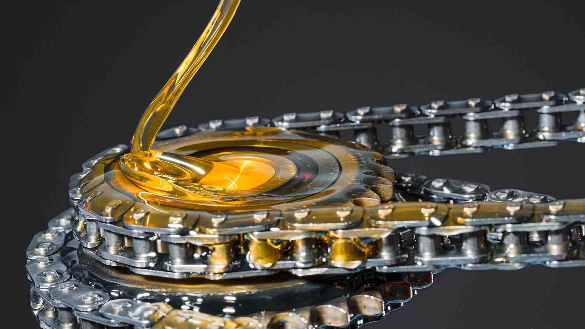 Das Bild zeigt Öl. Es fließt auf eine Motorenkette. Diese Kette liegt auf dem Boden. Sie spiegelt sich im Boden wieder. Der Hintergrund dahinter ist schwarz. Das Bild dient als Sliderbild für den Portfolioeintrag BMW / MINI Engine Oil Highspeed von Panda Pictures.