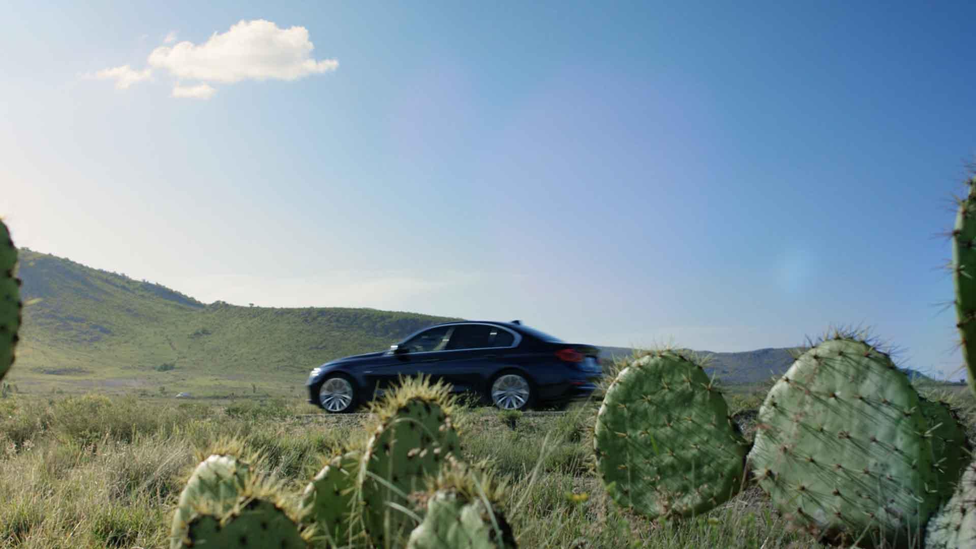 Das Bild zeigt die Wüste. Durch sie fährt ein schwarzes Auto. Vor dem Auto sind Kakteen erkennbar. Das Bild dient als Sliderbild für den Portfolioeintrag BMW Plant San Luis Potosí Mexico von Panda Pictures.