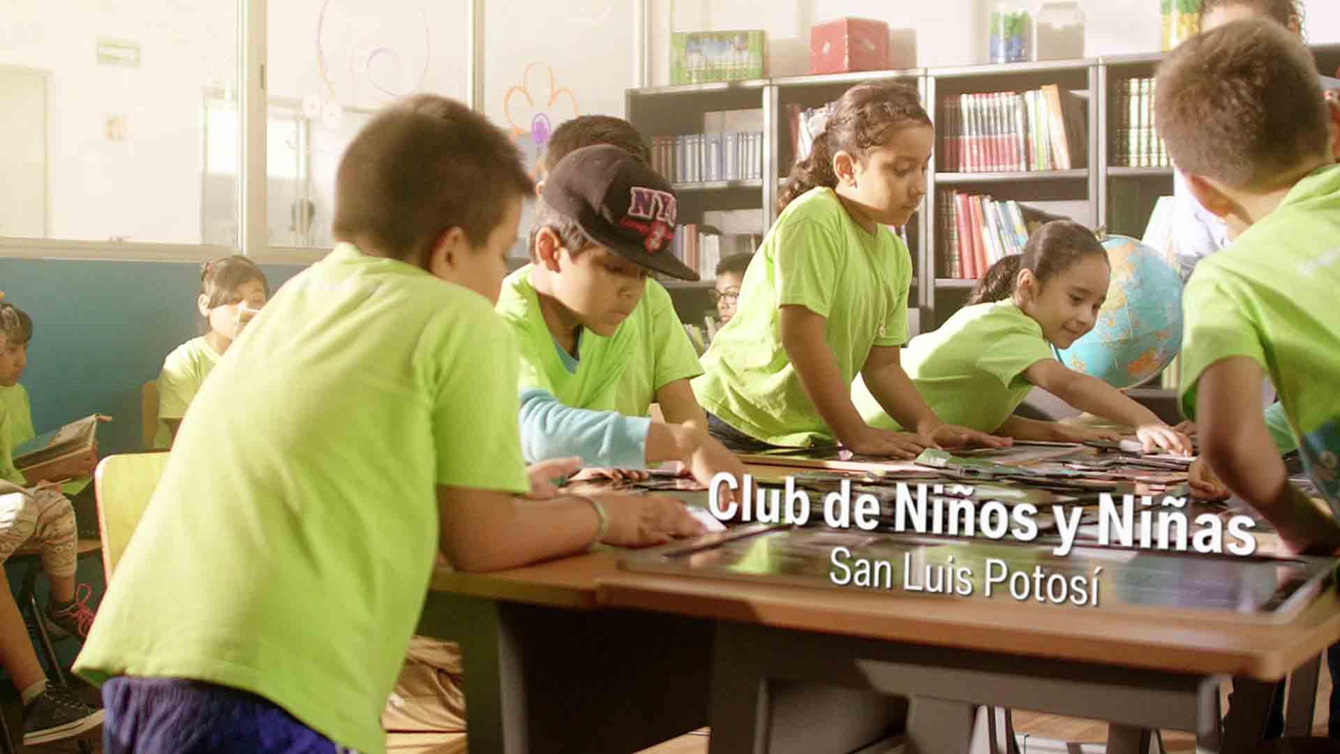 Das Bild zeigt einige Kinder die grüne T-shirts tragen. Sie sitzen an einem Schreibtisch. Hinter diesem Schreibtisch steht ein Bücherregal. Auf dem Schreibtisch ist ein animierter Text eingebettet. Das Bild dient als Sliderbild für den Portfolioeintrag BMW Plant San Luis Potosí Mexico von Panda Pictures.