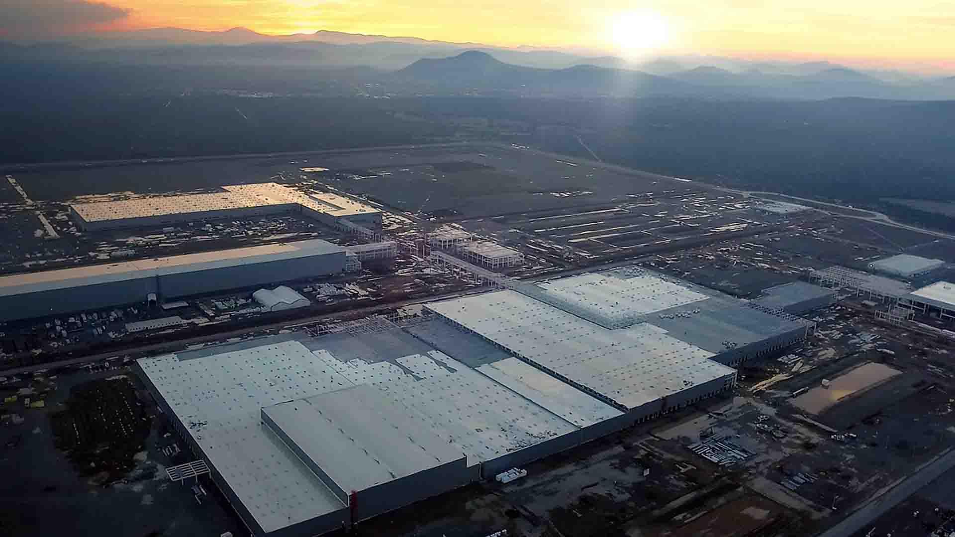 Das Bild zeigt eine Luftaufnahme. Auf dieser Luftaufnahme ist ein Werk von BMW zu erkennen. Der Hintergrund des Bildes ist durch Berge ausgefüllt. Hinter diesen Bergen geht die Sonne unter. Das Bild dient als Sliderbild für den Portfolioeintrag BMW Plant San Luis Potosí Mexico von Panda Pictures.