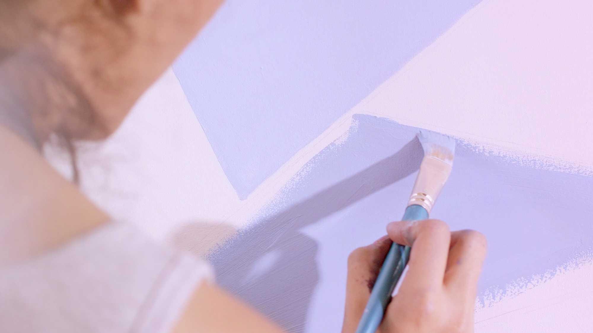 Das Bild zeigt den Ausschnitt einer Leinwand. Auf dieser wird gemalt. Ein Pinsel zeichnet blaue Dreiecke. Der Pinsel wird von einer Frau gehalten die in der linken Seite des Bildes zu sehen ist. Das Bild dient als Sliderbild für den Portfolioeintrag BMW Plant San Luis Potosí Mexico von Panda Pictures.