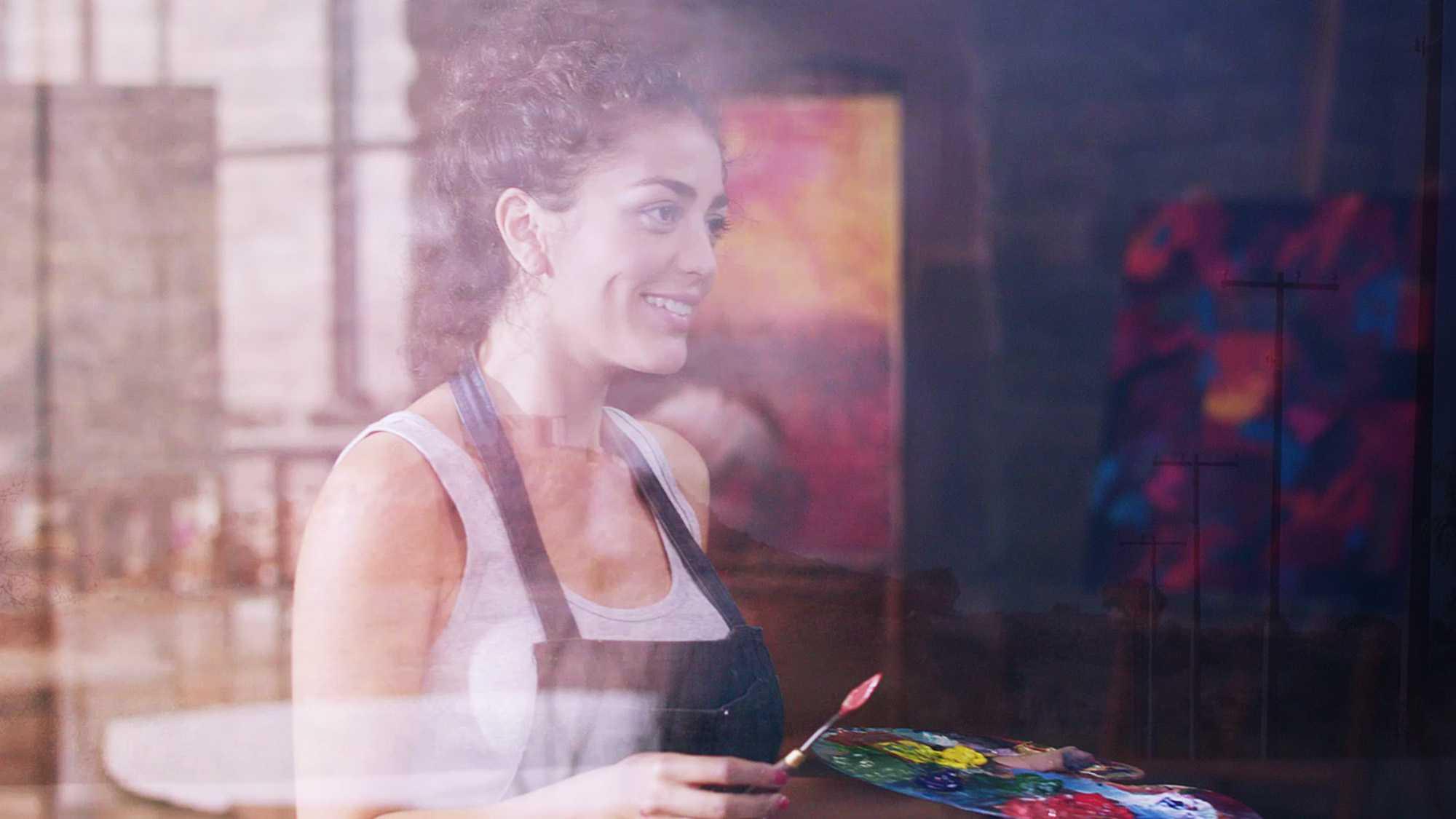 Das Bild zeigt eine Frau die sich in einem Atelier befindet. Sie hält ein Stück Holz in der Hand mit Hilfe dessen sie Farben zusammen mischt. In der anderen Hand hält sie einen Pinsel. Hinter ihr steht ein Gemälde. Das Bild dient als Sliderbild für den Portfolioeintrag BMW Plant San Luis Potosí Mexico von Panda Pictures.