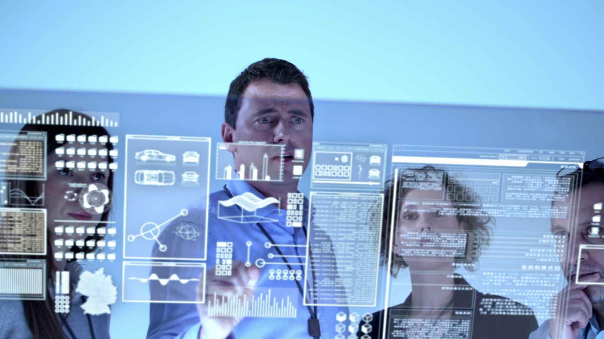 Das Bild zeigt zwei Männer und zwei Frauen. Sie stehen vor einer Art Bildschirm, dieser entstand durch eine Projektion. Auf dieser Projektion sind verschiedene Seiten zu sehen, die im Zusammenhang mit einem Fahrzeugbau stehen. Das Bild dient als Sliderbild für den Portfolioeintrag BMW QMT von Panda Pictures.