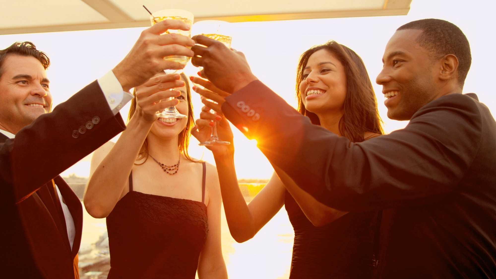Das Bild zeigt eine Gruppe Menschen. Zwei Männer und zwei Frauen stehen im Kreis und stoßen mit Sektgläsern an. Hinter ihnen scheint die Sonne. Sie tragen Kleidung fürs Büro. Das Bild dient als Sliderbild für den Portfolioeintrag H1 Fond von Panda Pictures.