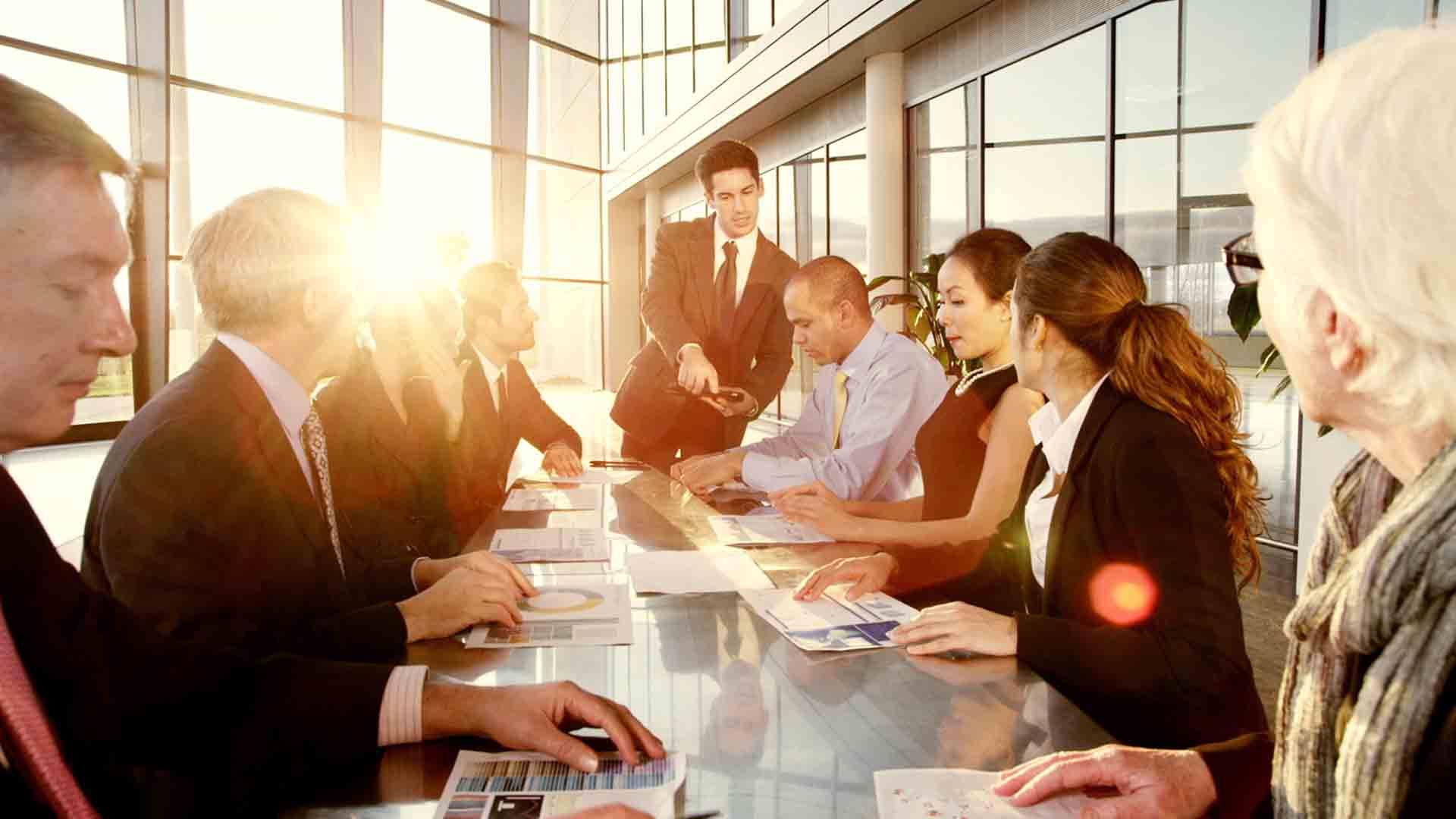 Das Bild zeigt einen langen Tisch. Dieser steht in einem Meetingraum. Um den Tisch herum sitzen Menschen in Business Kleidung. Am Ende des Tisches steht ein Mann in Anzug. Die Wände sind von vielen Fenstern geziert, die Sonne scheint herein. Das Bild dient als Sliderbild für den Portfolioeintrag H1 Fond von Panda Pictures.