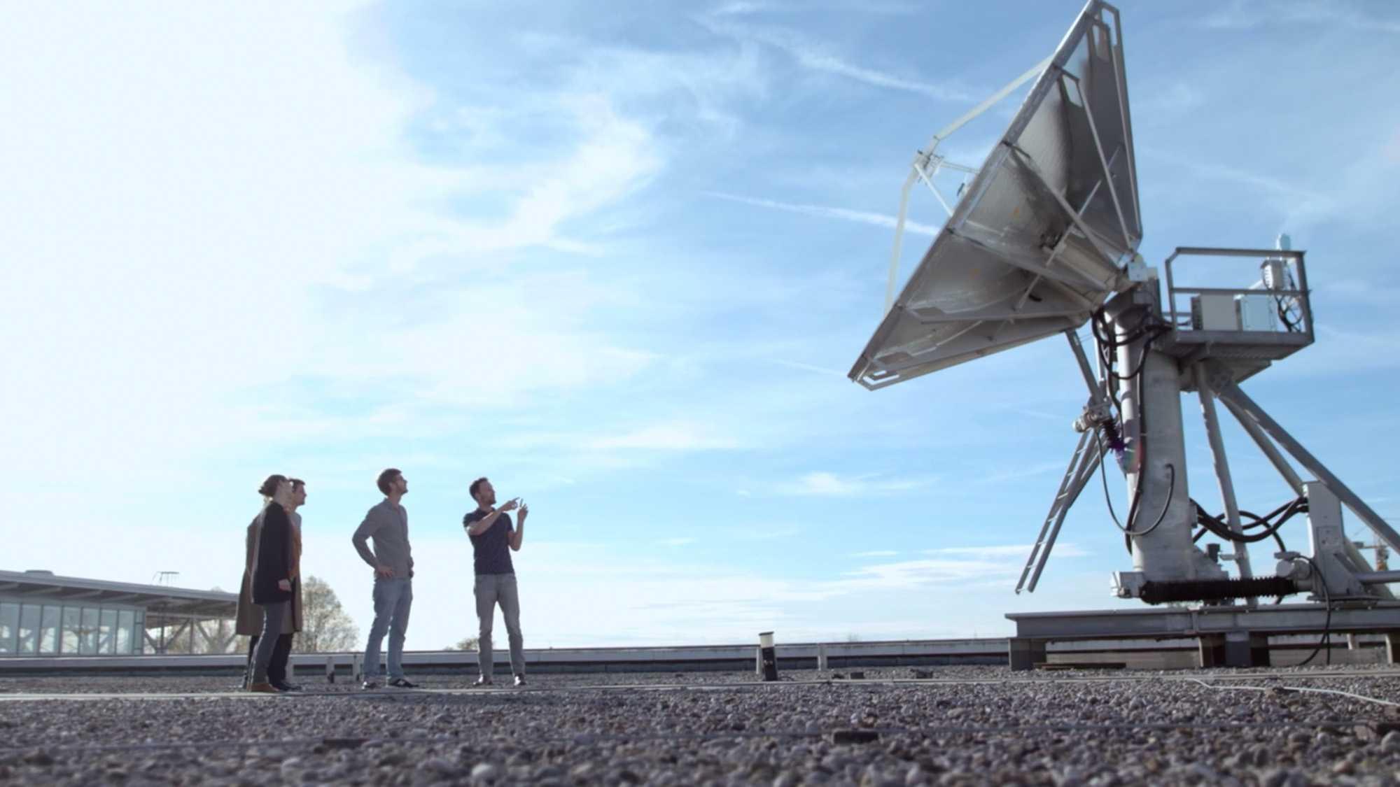 Das Bild zeigt auf der rechten Seite einen großen Satelliten stehen. Vor ihm stehen drei Männer, die sich unterhalten. Sie stehen auf einem asphaltierten Platz. Hinter ihnen steht ein Gebäude. Ein blaugefärbter Himmel ziert den Hintergrund. Das Bild dient als Sliderbild für den Portfolioeintrag Munich Aerospace Imagefilm von Panda Pictures.