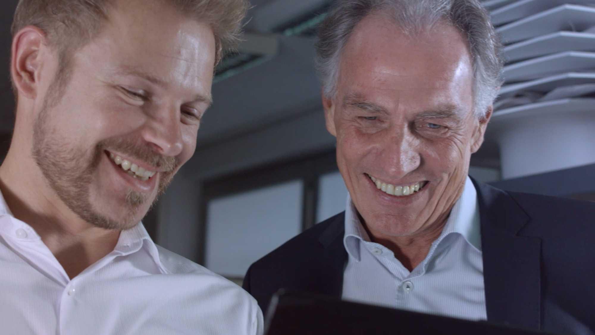 Das Bild zeigt zwei Männer die in ein Tablet starren. Sie sind beide am lachen. Beide tragen ein weißes Hemd. Der Mann der auf der rechten Seite steht trägt zu seinem Hemd noch ein schwarzes Sakko. Das Bild dient als Sliderbild für den Portfolioeintrag Munich Aerospace Imagefilm von Panda Pictures.