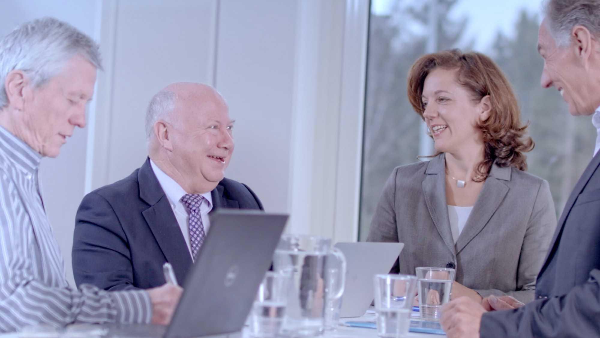 Das Bild zeigt drei Männer und eine Frau die an einem Tisch sitzen. Auf der linken Seite sitzen zwei Männer auf der rechten Seite sitzt die Frau und der dritte Mann. Auf dem Tisch stehen Gläser und eine Wasserkaraffe sowie zwei Laptops. Das Bild dient als Sliderbild für den Portfolioeintrag Munich Aerospace Imagefilm von Panda Pictures.