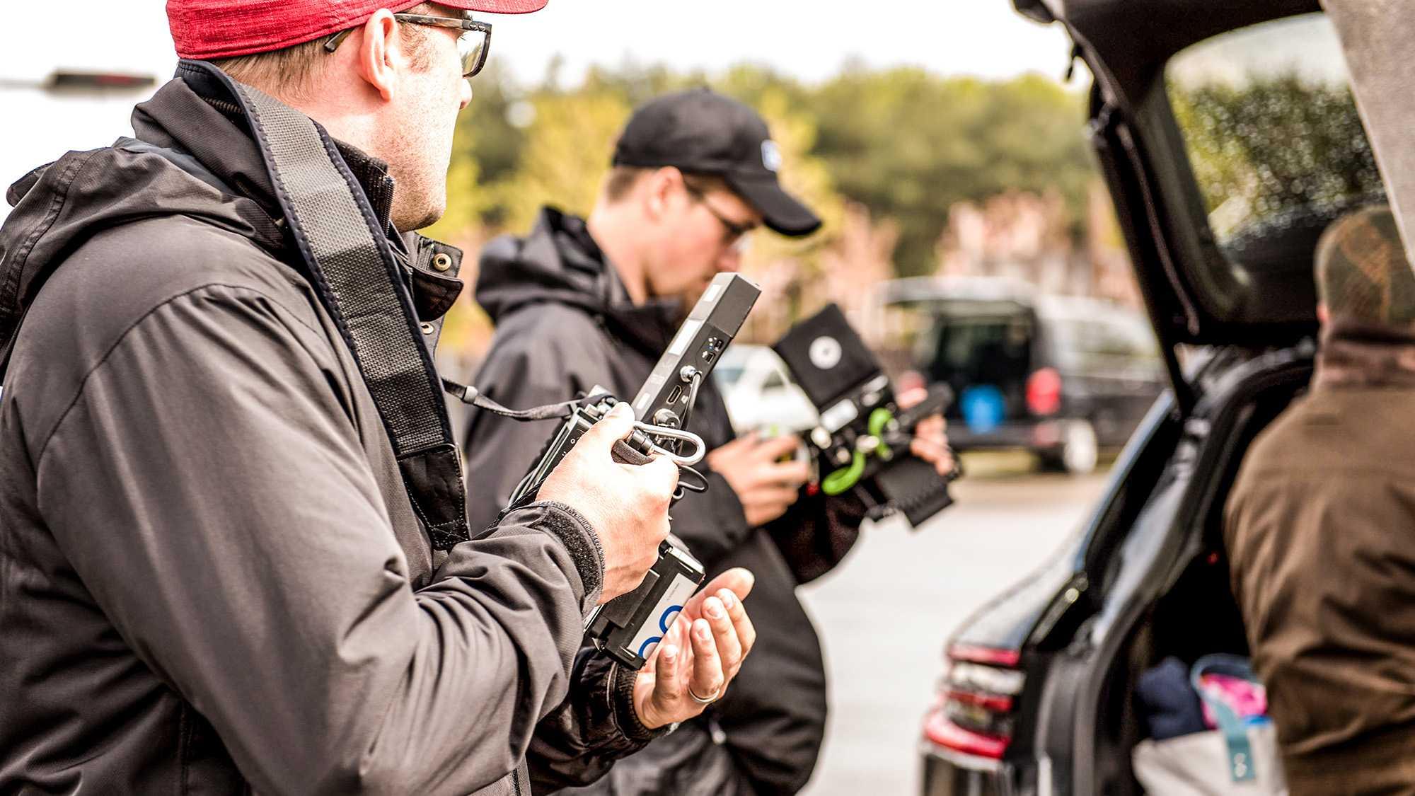 Das Bild zeigt einen Mann, der einen Kameramonitor in seiner Hand hält. Er trägt eine rote Mütze. Man sieht in von der Seite. Vor ihm, verschwommen erkennbar, sitzt ein Mann in einem Kofferraum. Hinter ihm steht ein Mann. Das Bild dient als Sliderbild für den Portfolioeintrag RECARO Child Safety Zero.1 Elite von Panda Pictures.