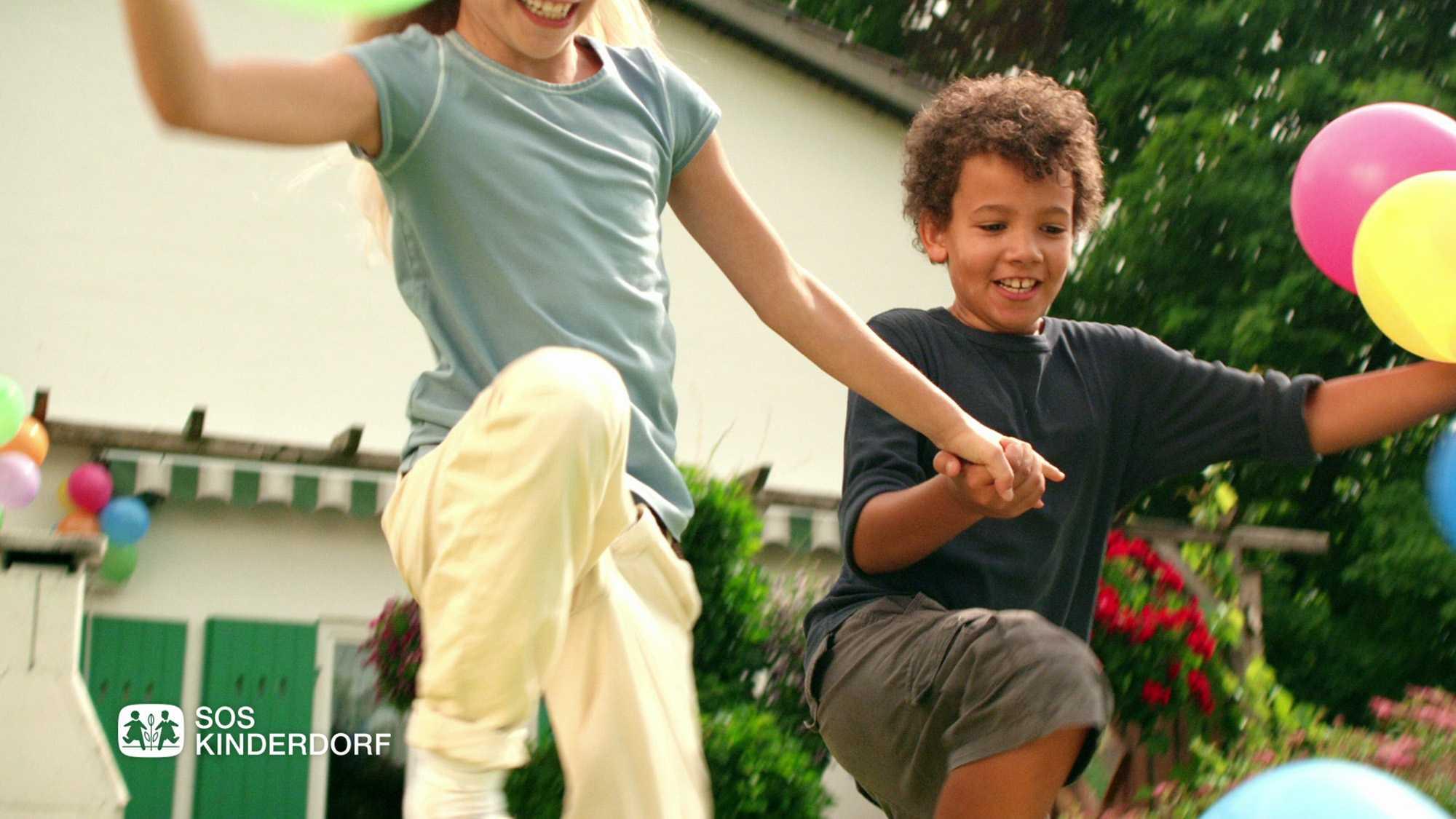 Das Bild zeigt zwei Kinder. Ein Junge springt auf der rechten Seite des Bildes in die Luft, er hält zwei Ballons in der Hand. Neben ihm springt ein Mädchen in die Luft. Sie halten sich an den Händen. Das Bild dient als Sliderbild für den Portfolioeintrag SOS-Kinderdorf Sommer von Panda Pictures.