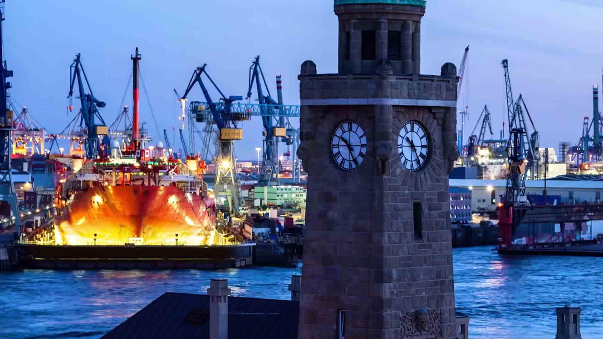 Das Bild zeigt einen Kirchturm. Dieser trägt eine Uhr. Dahinter sieht man einen Hafen. In dem Hafen stehen viele Schiffe und Kräne. Sie sind beleuchtet, da es Abend ist. Das Bild dient als Sliderbild für den Portfolioeintrag SupplyOn - Supply Chain Management Imagefilm von Panda Pictures.